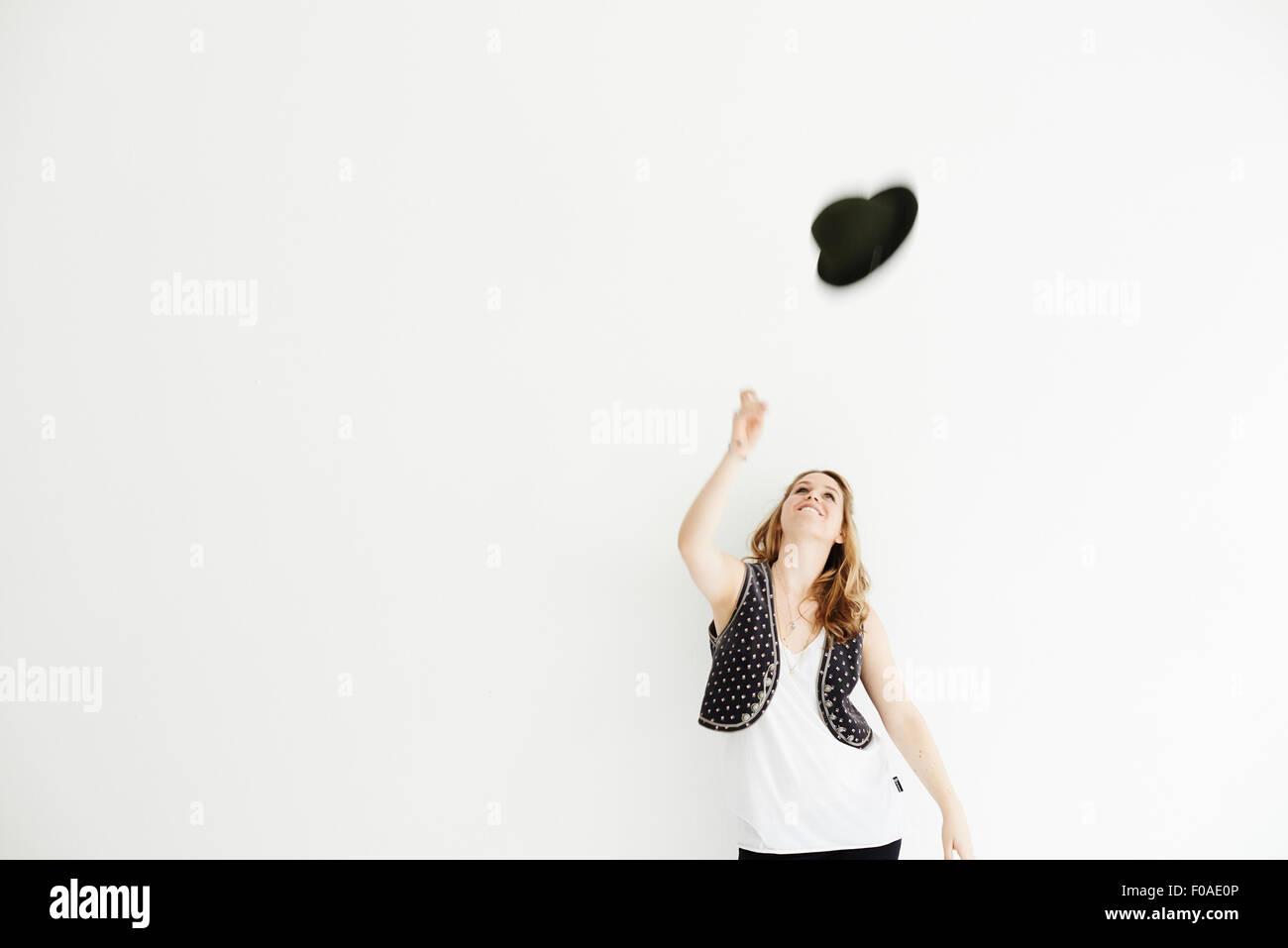Mujer adulta media arrojando el sombrero en el aire, espacio de copia Imagen De Stock