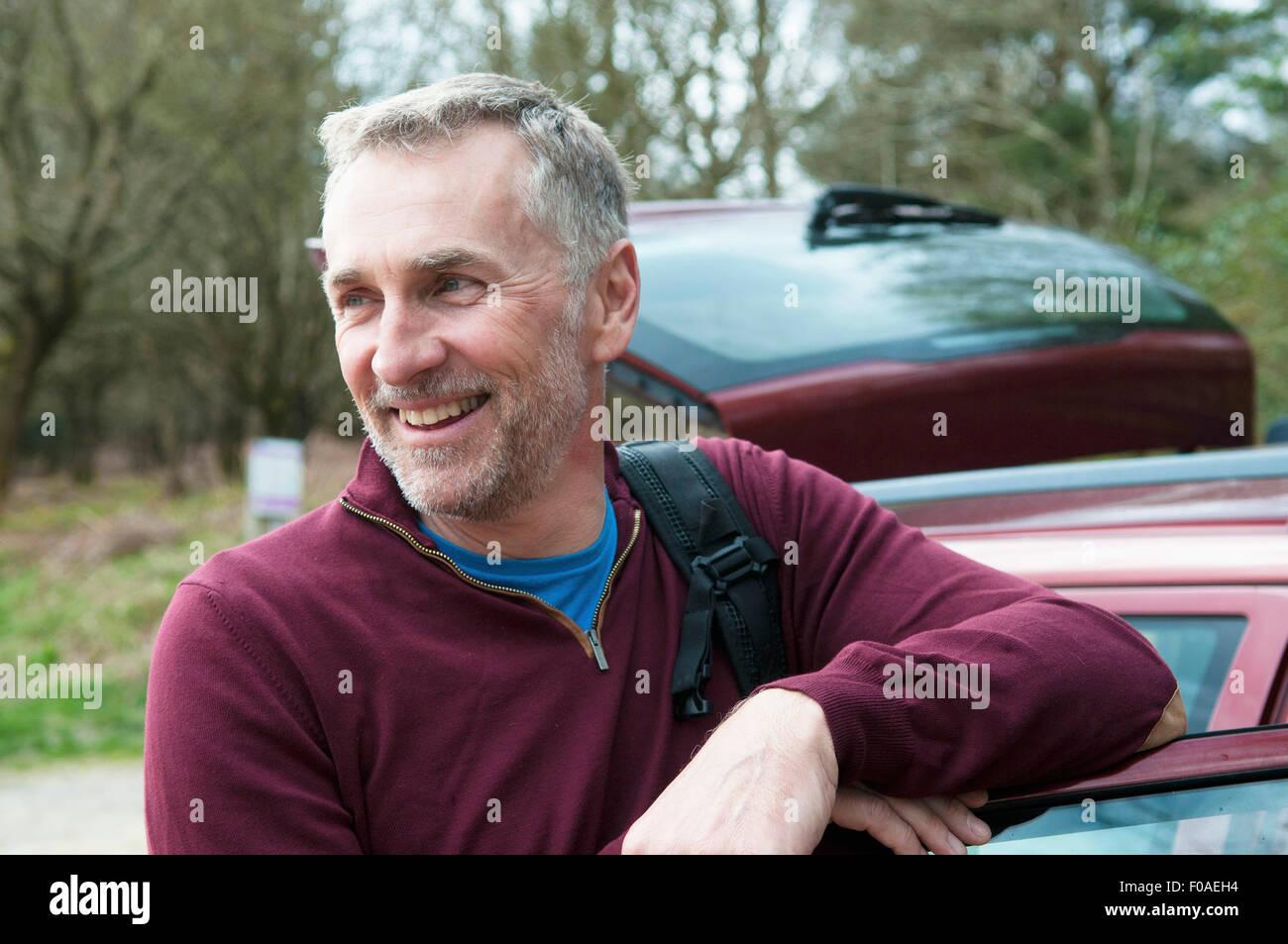 Retrato del excursionista macho apoyado contra la puerta de coche Imagen De Stock