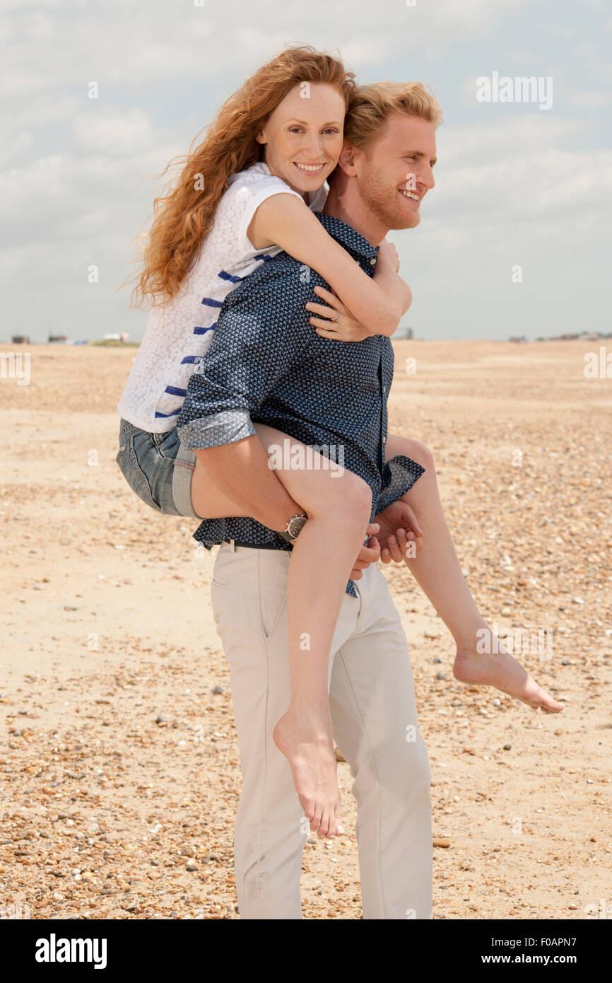 Hombre haciendo novia a cuestas en la playa. Imagen De Stock