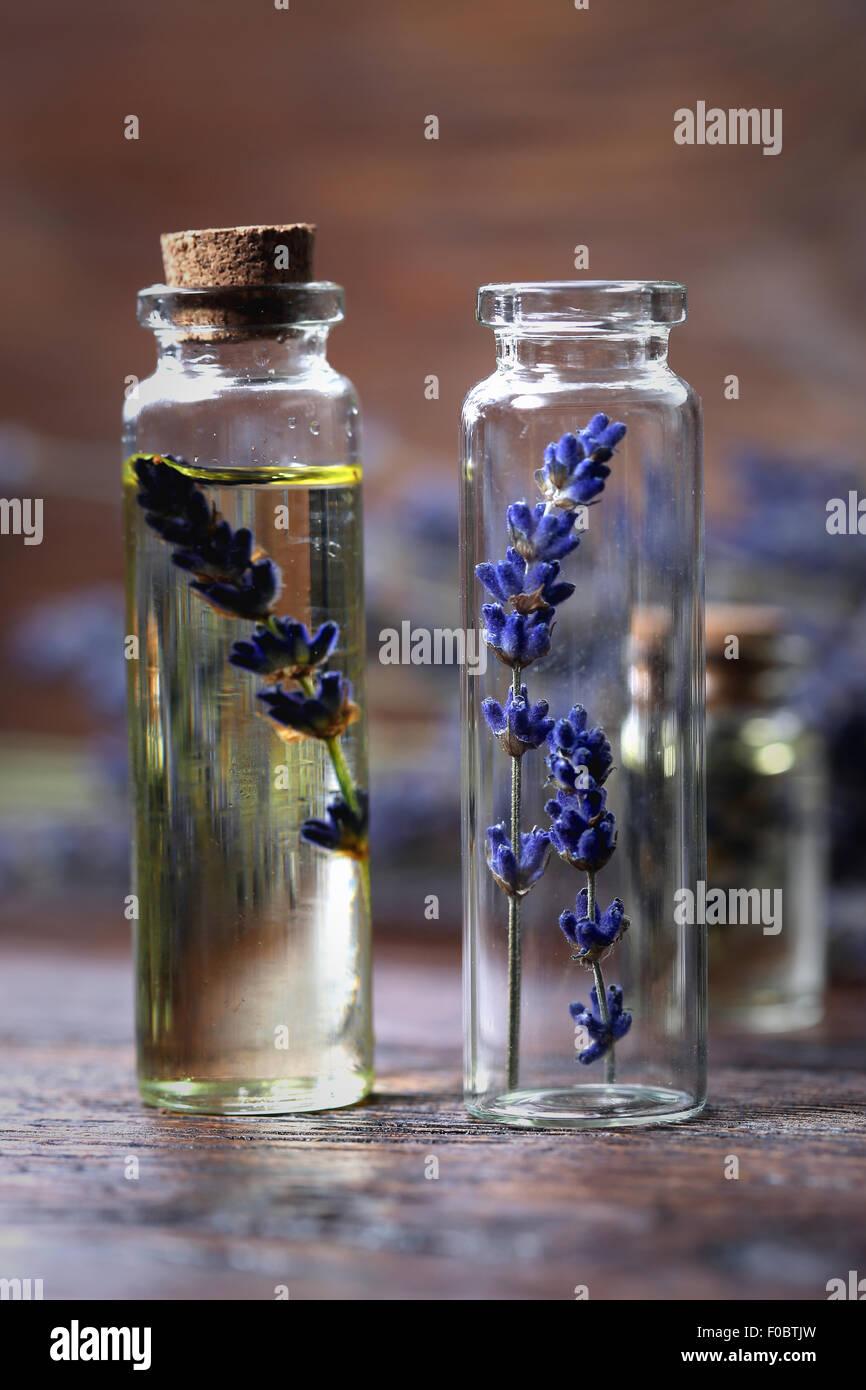 Aceite de lavanda en una botella de vidrio sobre una mesa de madera Imagen De Stock
