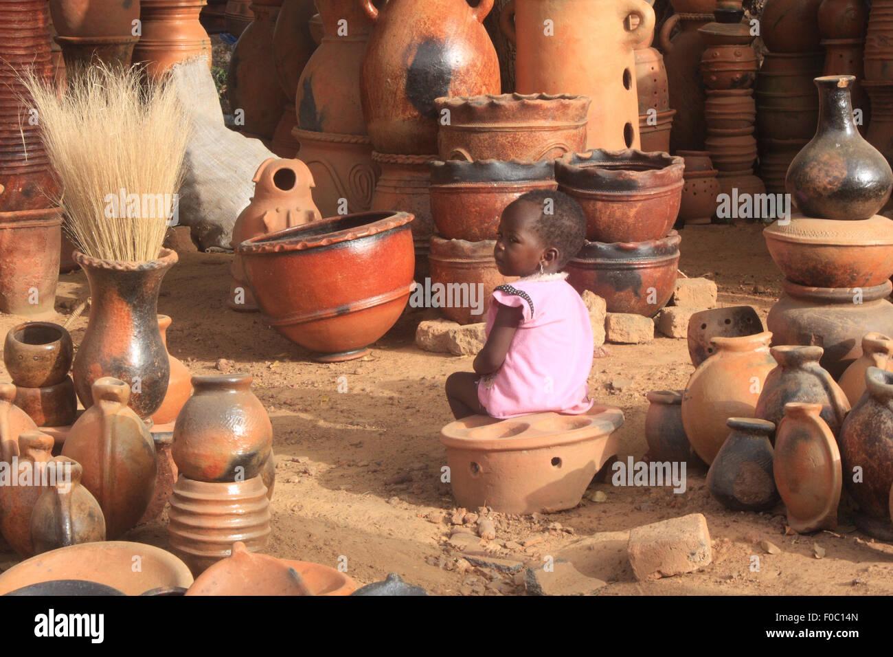 BANDIAGARA, Malí - Octubre 5, 2008: La niña no identificada en un taller de alfarería en bandiagara en la región Foto de stock