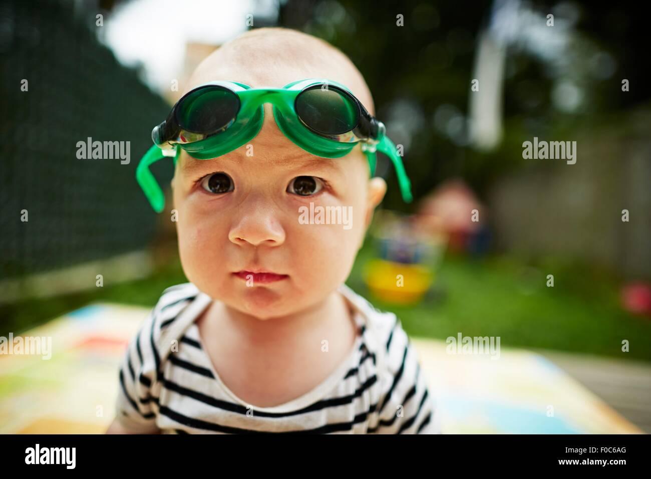 Close Up retrato de Baby Boy mirando a la cámara usando gafas de natación Imagen De Stock
