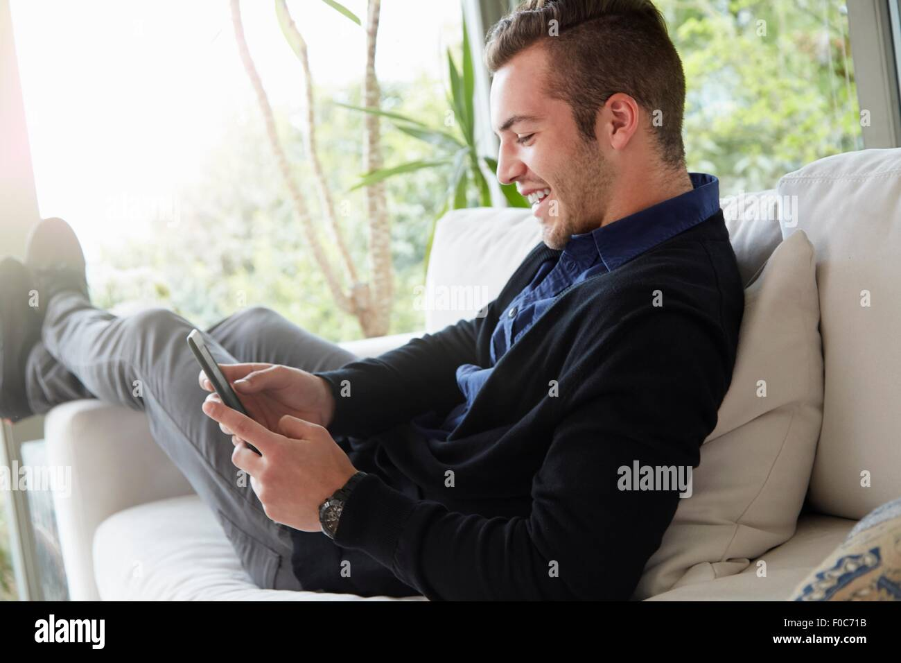 Retrato del hombre relajado en el sofá con los pies hacia arriba mirando al dispositivo de lectura digital Imagen De Stock