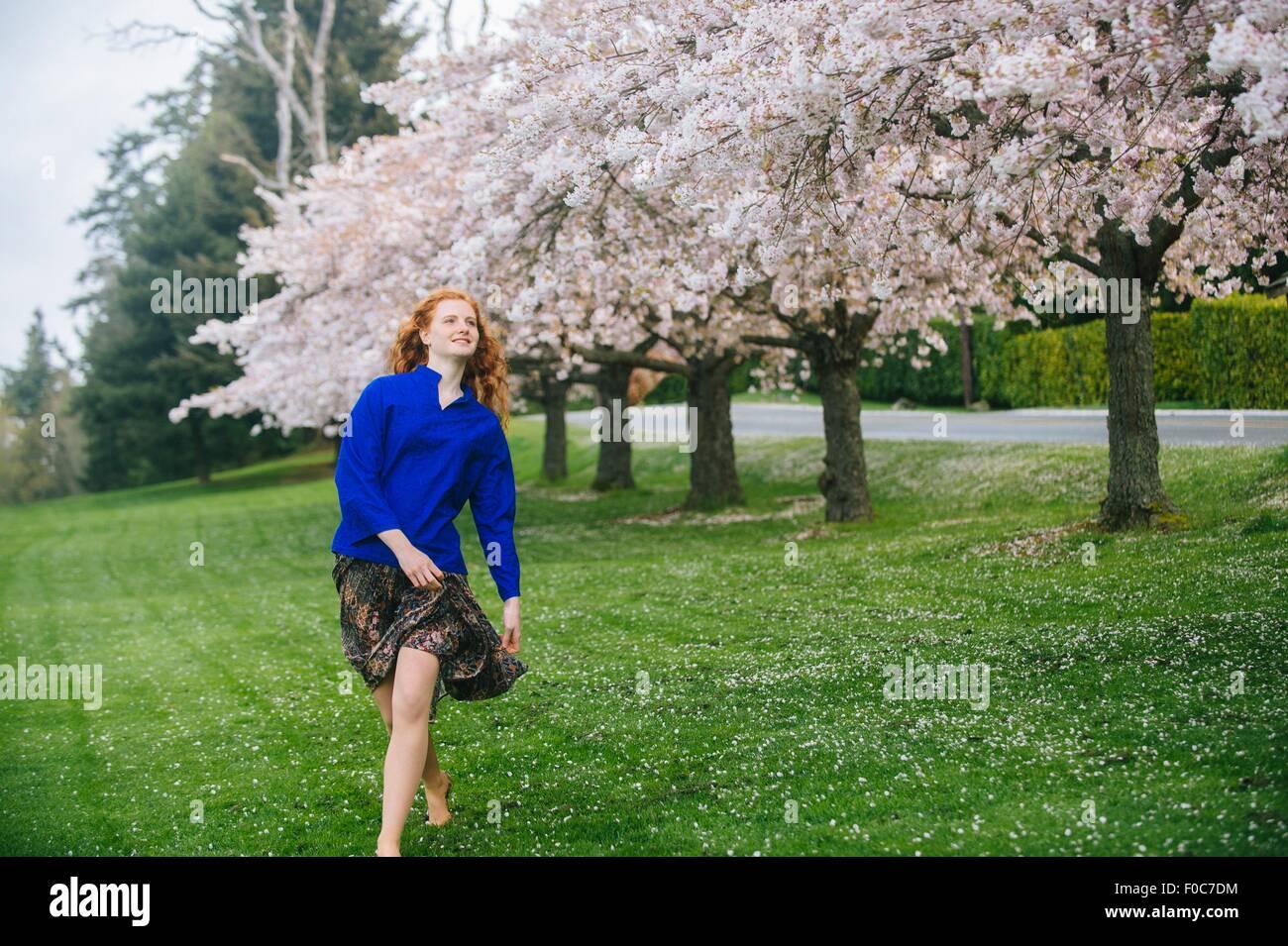 Mujer joven bailar descalzo en primavera park Foto de stock