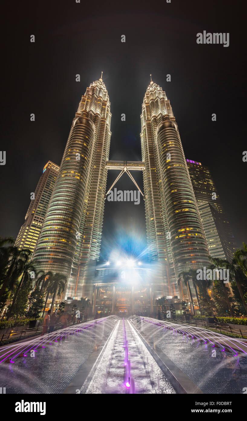 Fuente delante de la torre Petronas iluminada por la noche, Kuala Lumpur, Malasia Imagen De Stock