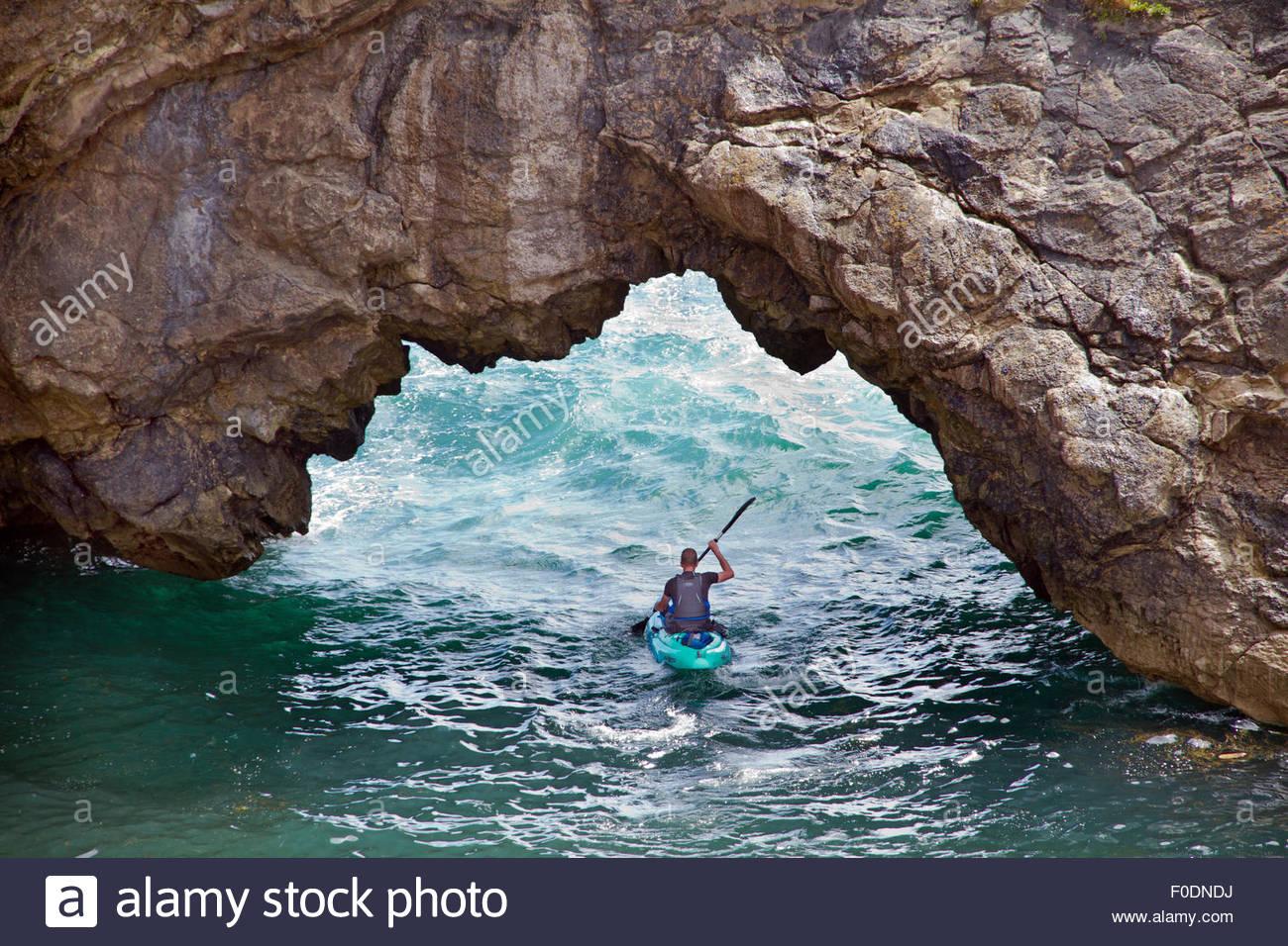 Hombre kayak aunque brecha en el muro acantilado. Imagen De Stock