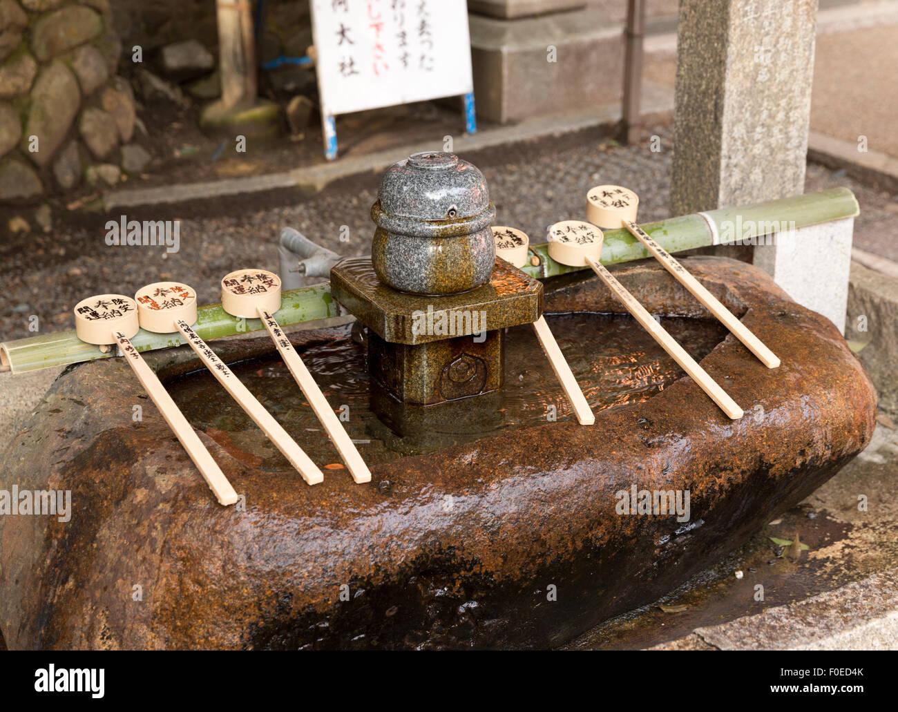 Fuente de agua y cucharones en santuario sintoísta Fushimi Inari en Kyoto, Japón Imagen De Stock