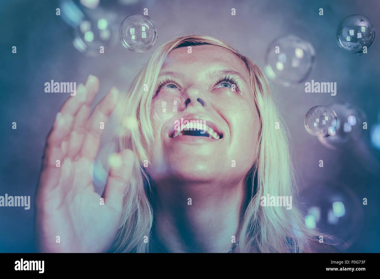 Hermosa rubia chica sonriente mirando hacia arriba y disfrutar de fabulosas maravillas. Imagen De Stock