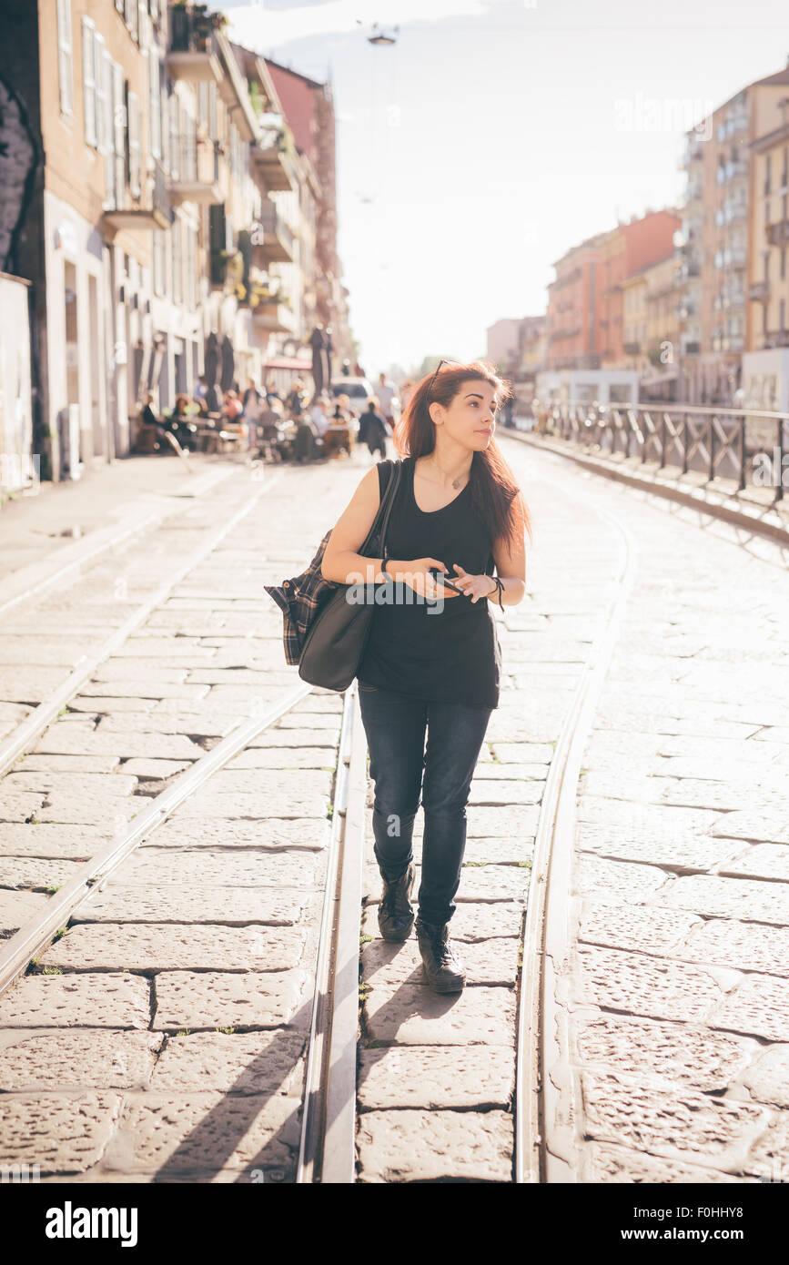 Hermosa joven niña de pelo marrón rojizo caucásica caminar usando el smartphone con vistas - desenfado, Imagen De Stock