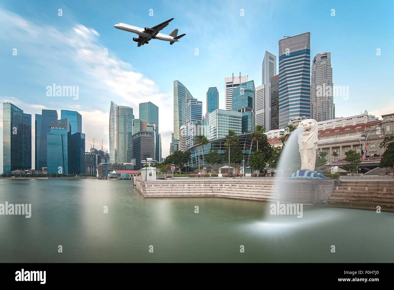 Viajes y Transporte, concepto - avión sobrevolando la ciudad de Singapur en la mañana tiempo Imagen De Stock