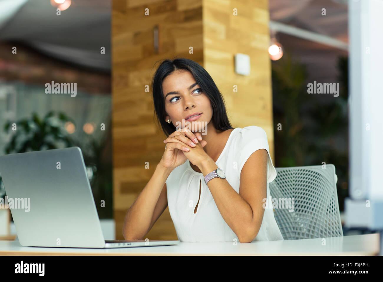 Retrato de una empresaria pensativo sentado a la mesa en la oficina y mirar lejos Imagen De Stock