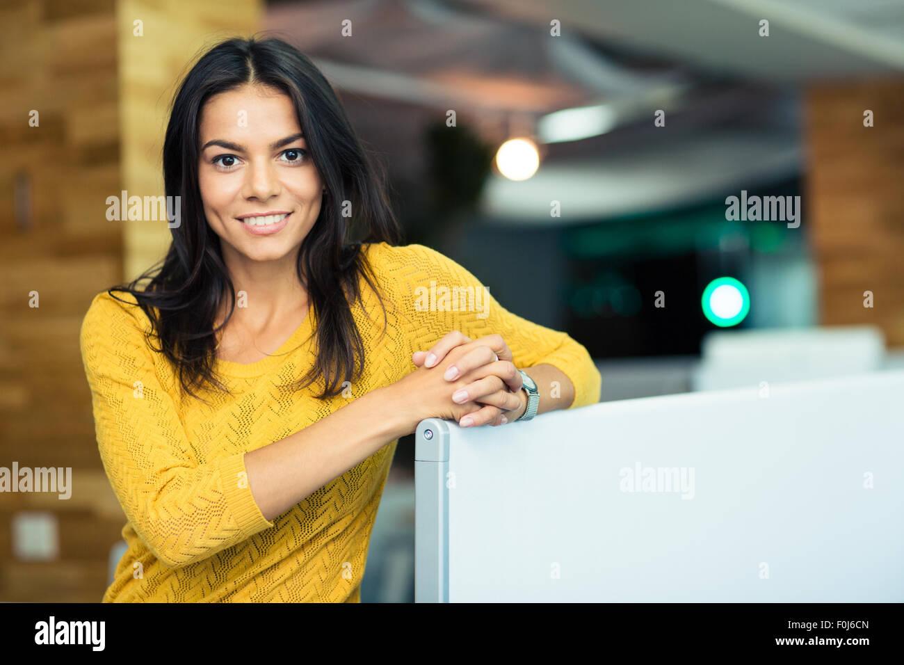 Retrato de una hermosa feliz empresaria en la oficina permanente y mirando a la cámara Imagen De Stock