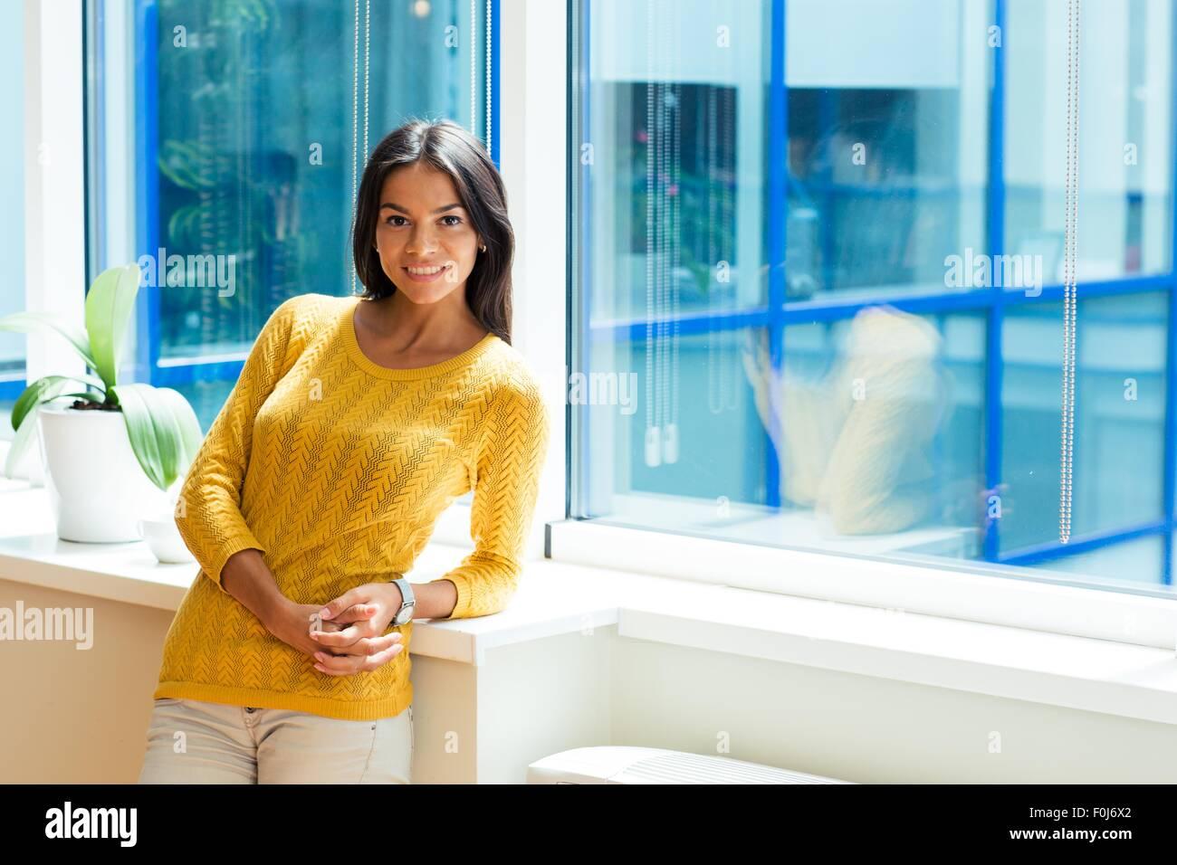 Sonriente atractiva empresaria de pie cerca de la ventana en la oficina y mirando a la cámara Imagen De Stock