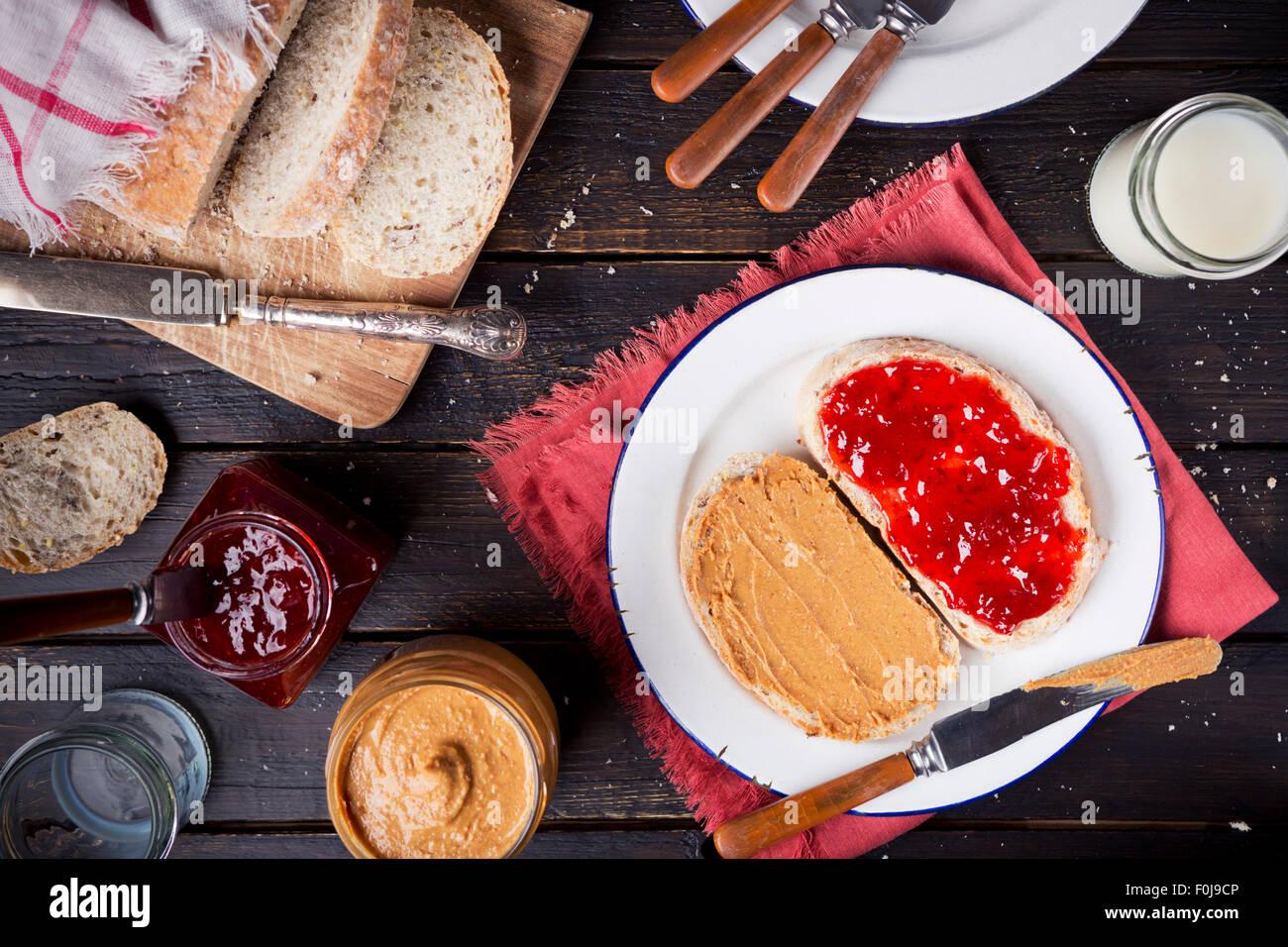 Sándwich de mantequilla de maní y mermelada en una mesa de estilo rústico. Fotografiado desde directamente Imagen De Stock