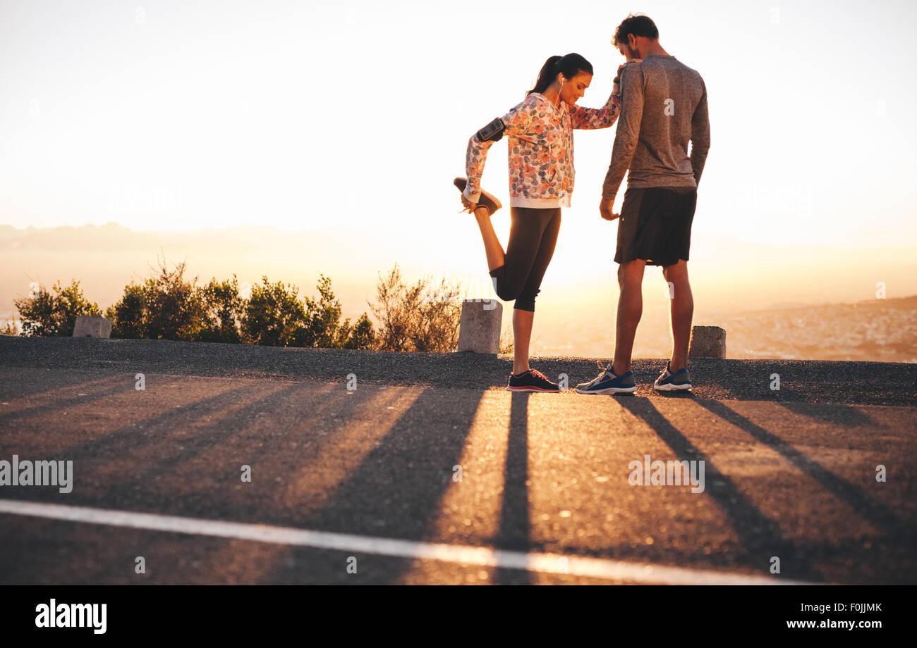 Disparó al aire libre de colocar los jóvenes deportistas estiramientos antes de correr juntos en la mañana. Imagen De Stock