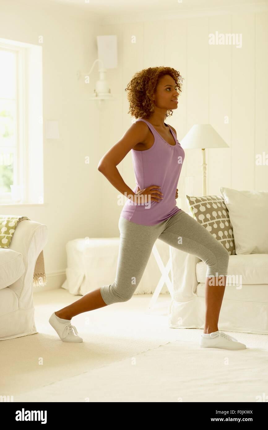 Mujer en polainas y sin mangas realizar ejercicio lunge avance, vista lateral Imagen De Stock