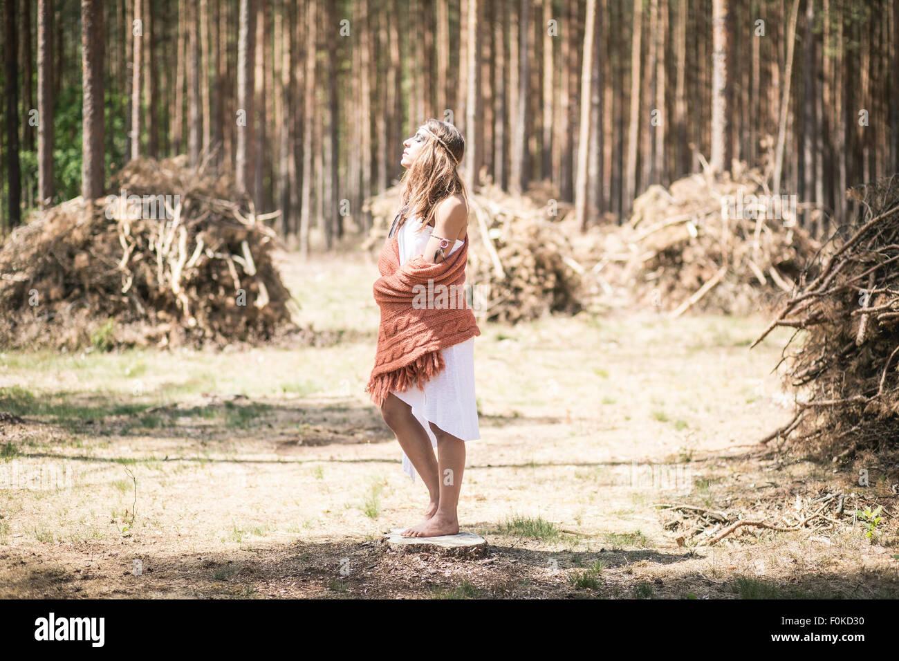 Mujer joven de pie en el bosque disfrutando de la tranquilidad Imagen De Stock