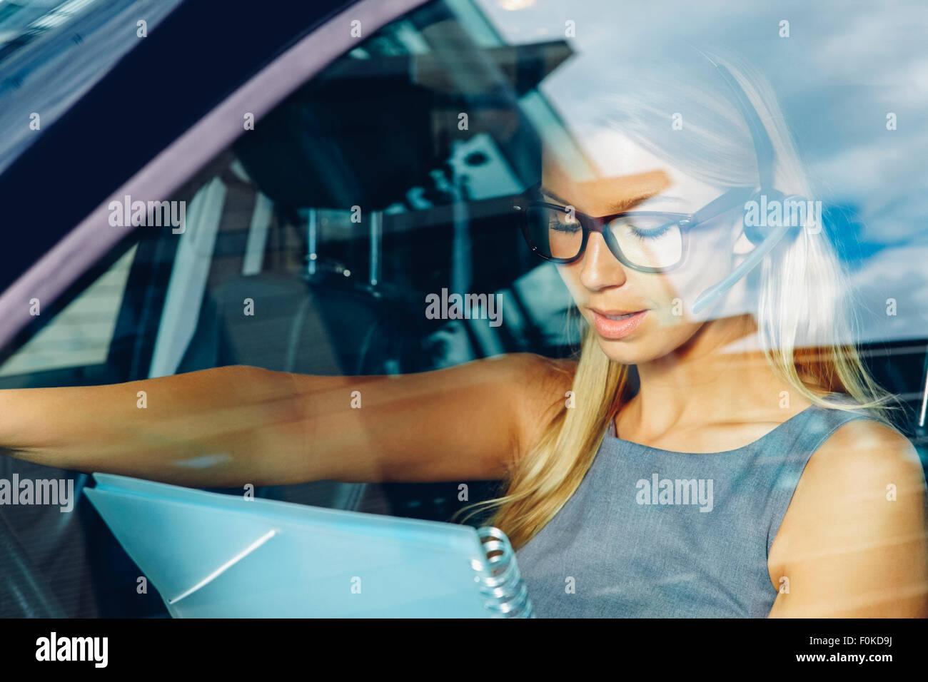 La empresaria vistiendo dispositivo inalámbrico Bluetooth en el coche Imagen De Stock