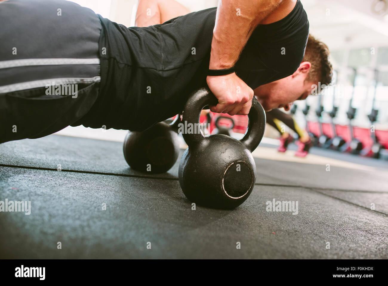 Atleta CrossFit HACIENDO FLEXIONES SOBRE kettlebells Foto de stock