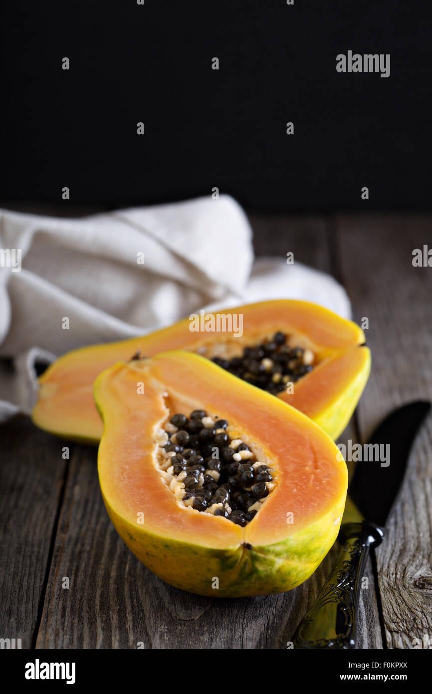 Cortar la fruta exótica de papaya sobre una tabla de madera Foto de stock