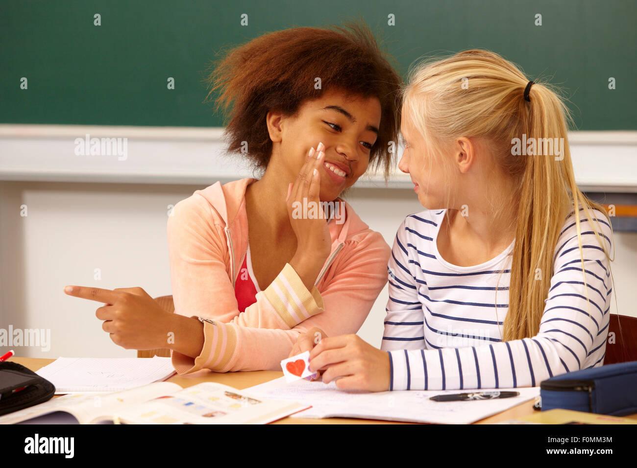 Dos niñas susurran sobre una carta de amor Foto de stock