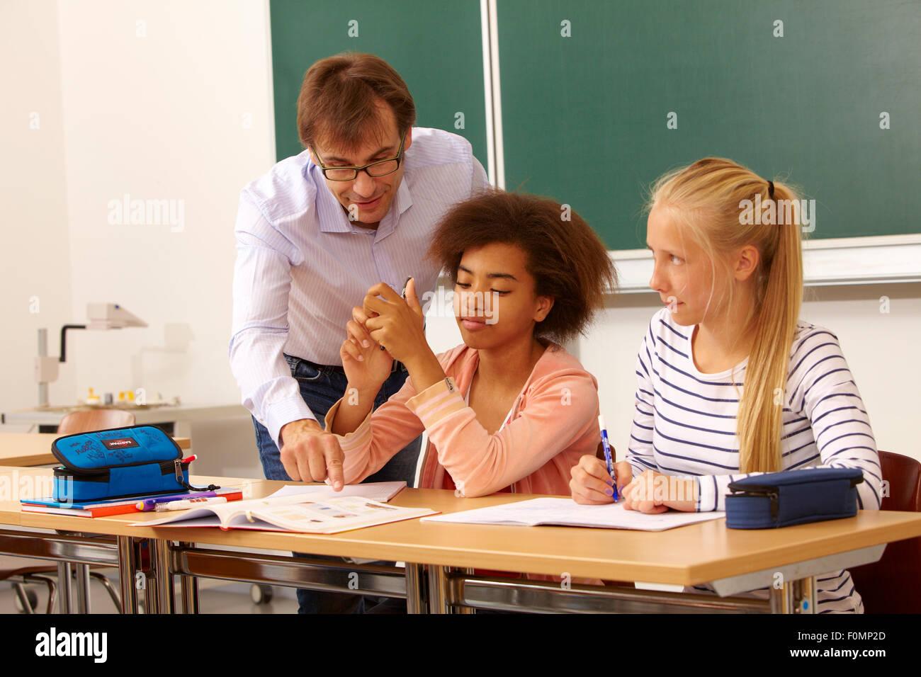 Maestro ayuda a dos alumnas en las lecciones Foto de stock
