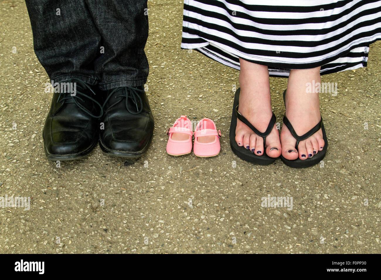 Un hombre y una mujer de los pies con un par de zapatos de bebé entre ellos. Imagen De Stock