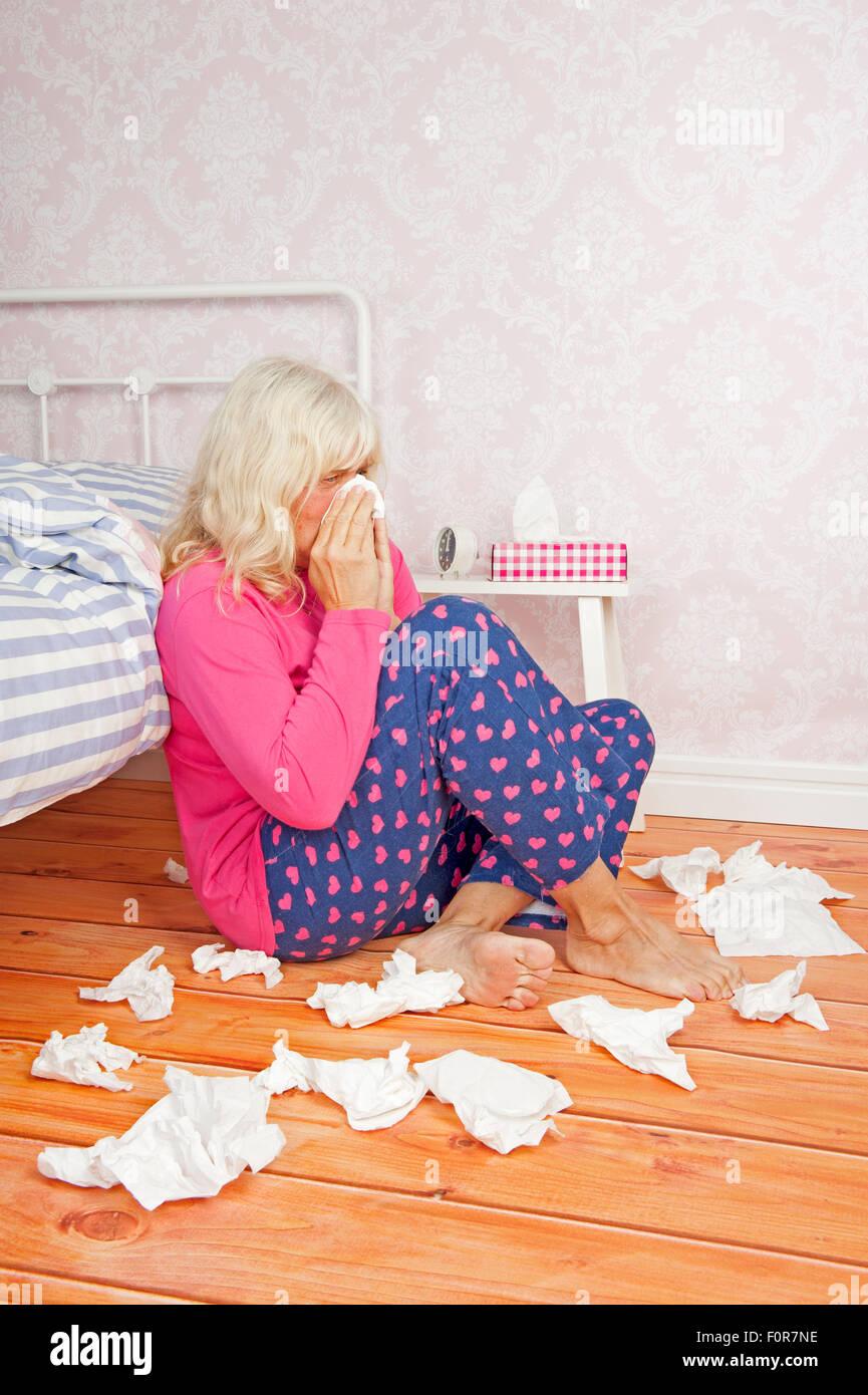 Mujer enferma con pijama rosa y tejidos sentada en el piso contra la cama Imagen De Stock