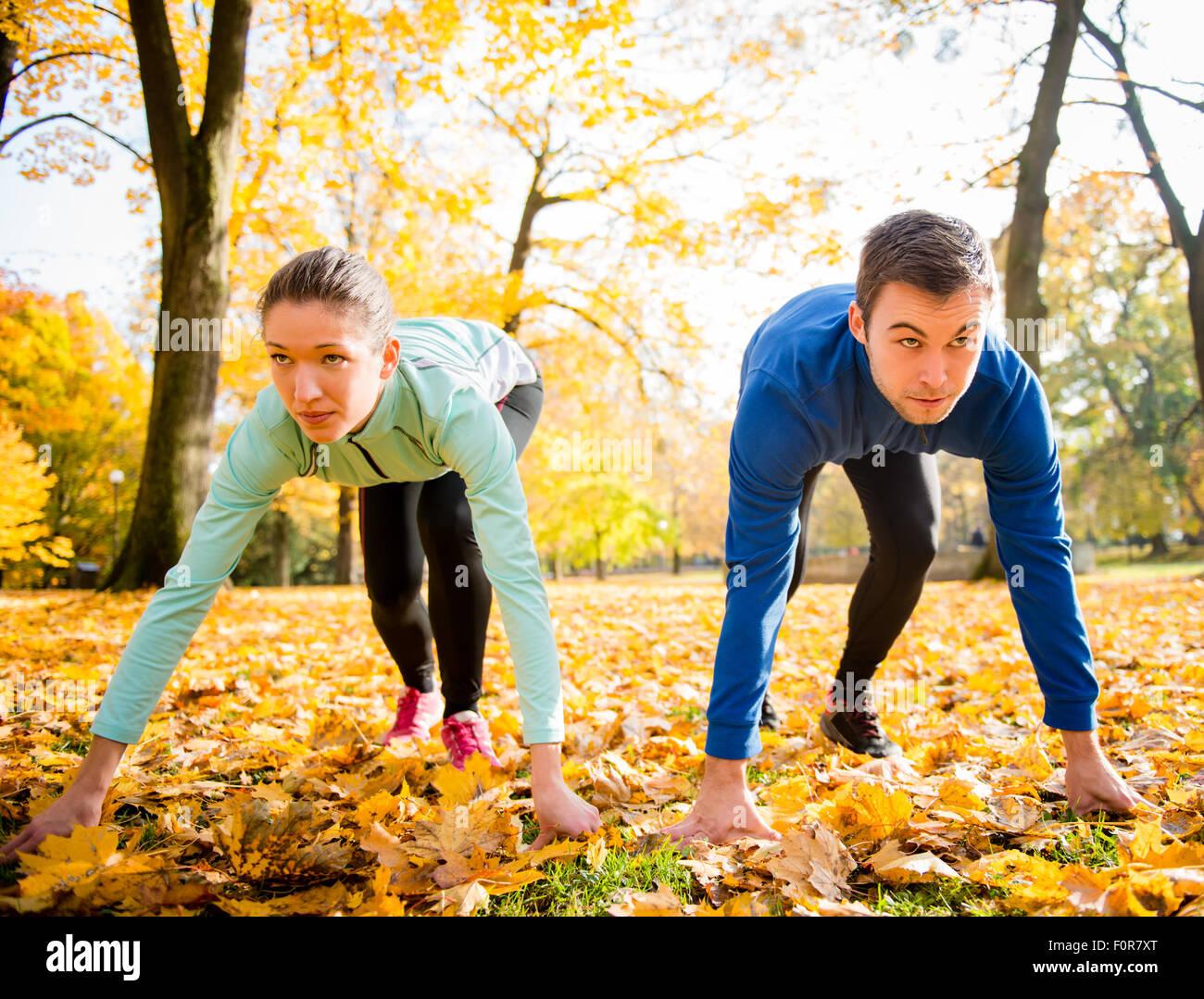Pareja joven en posición inicial preparado para correr en otoño la naturaleza Imagen De Stock