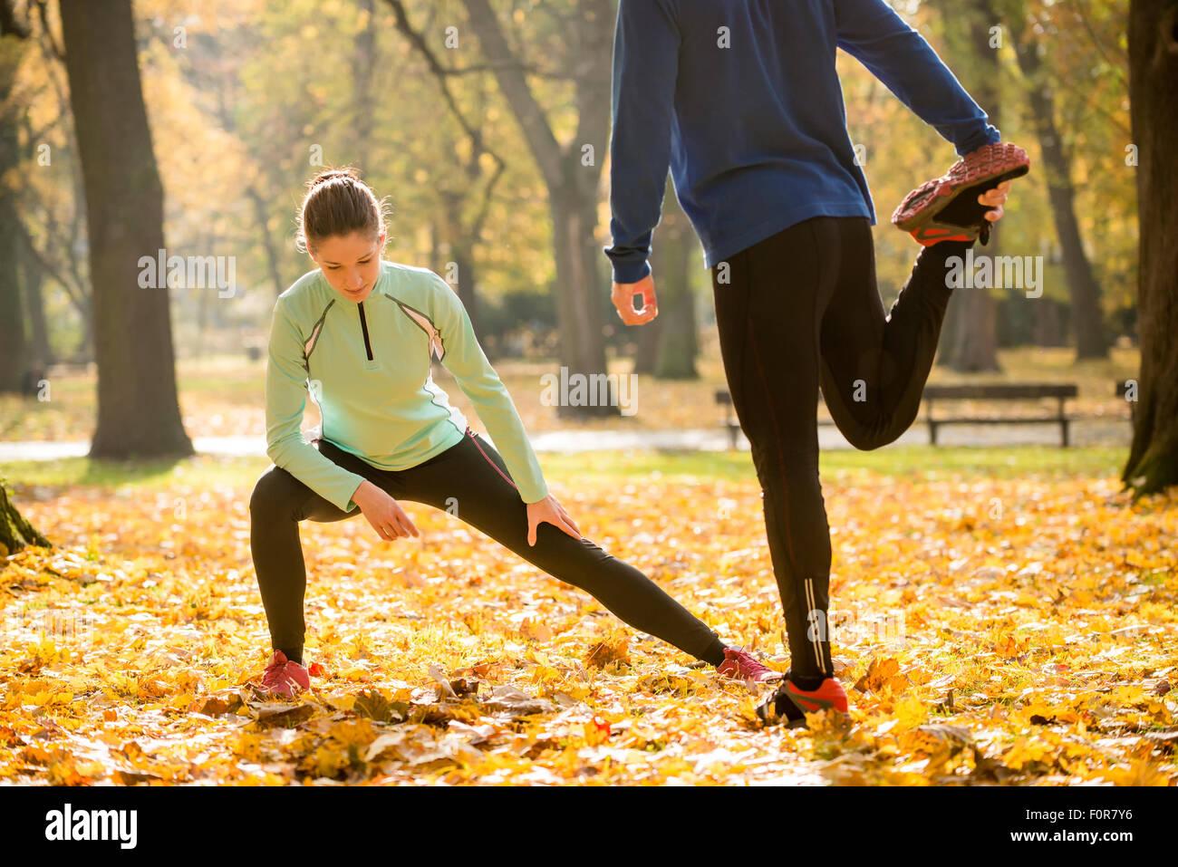 Pareja joven estirar las piernas antes de ejecutar en el otoño de la naturaleza Imagen De Stock