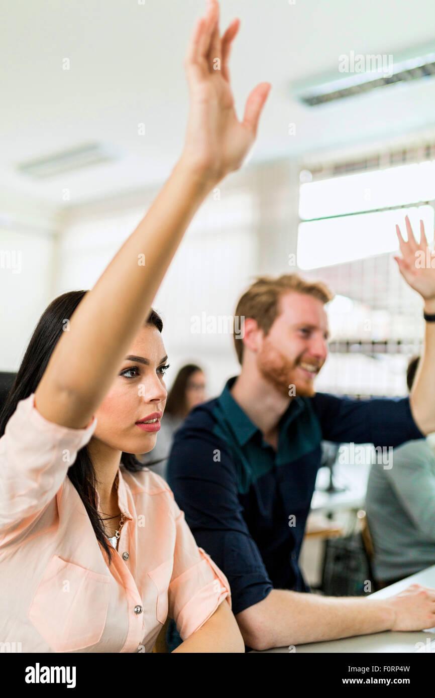 Hermosa joven y un hombre levantando las manos en el aula mientras está sentado en un escritorio Imagen De Stock