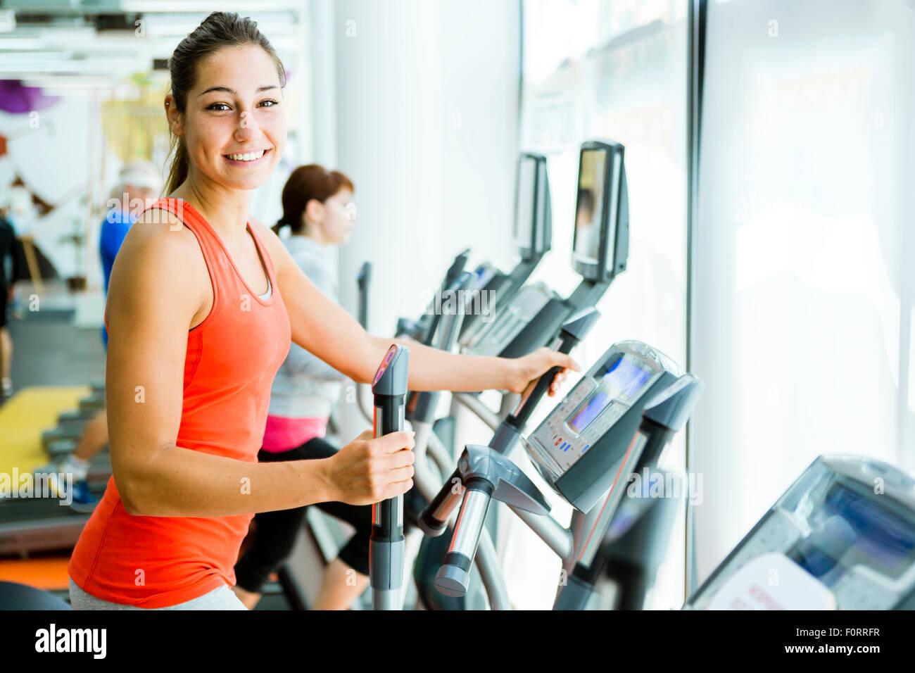 Colocar una mujer joven con un entrenador elíptico en un gimnasio y sonriente Imagen De Stock
