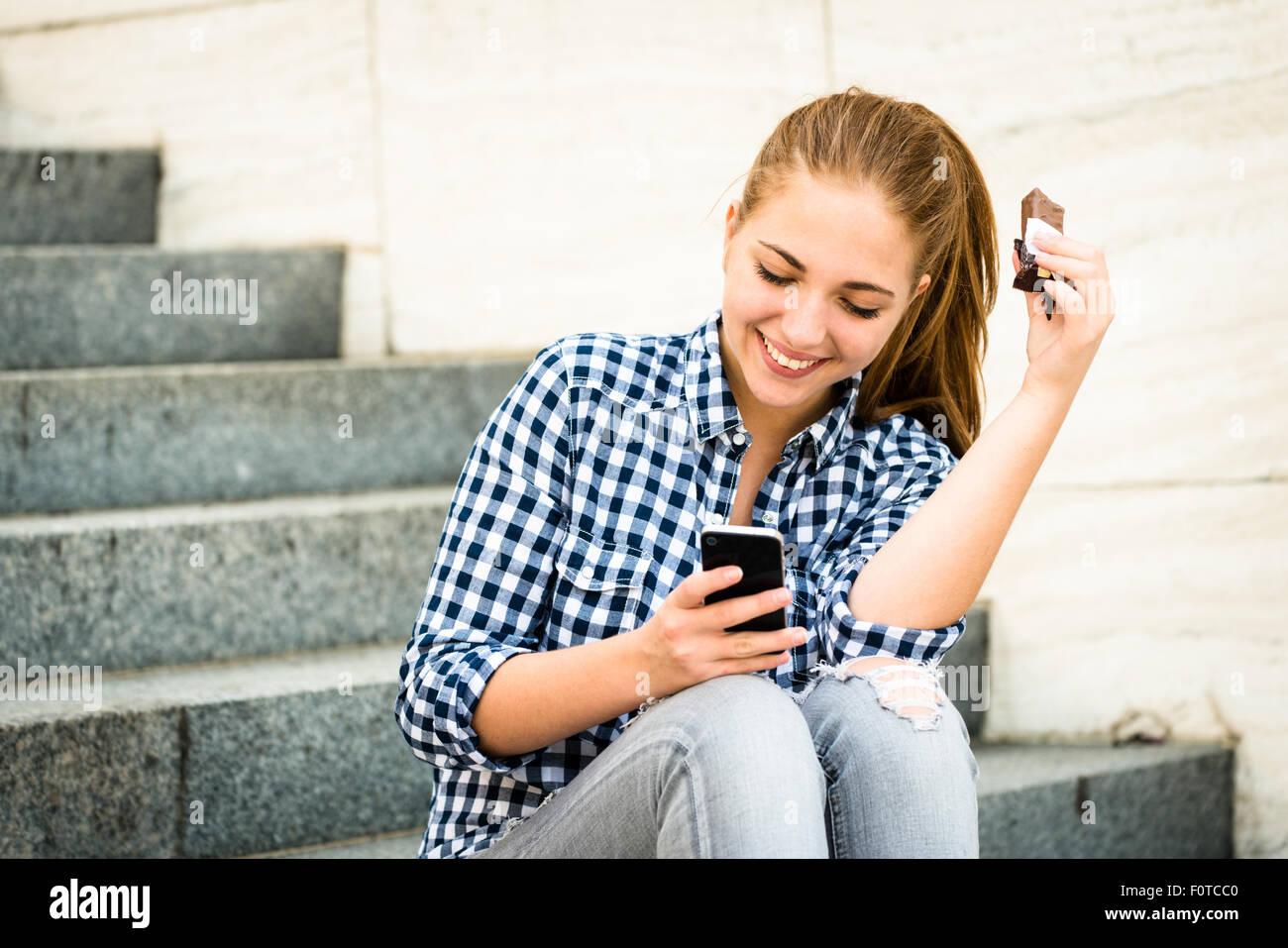 Adolescente - joven comer chocolate en la calle y buscando en el teléfono Foto de stock