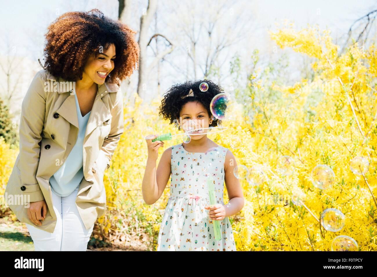 Vista frontal de la madre y la hija soplando burbujas Imagen De Stock
