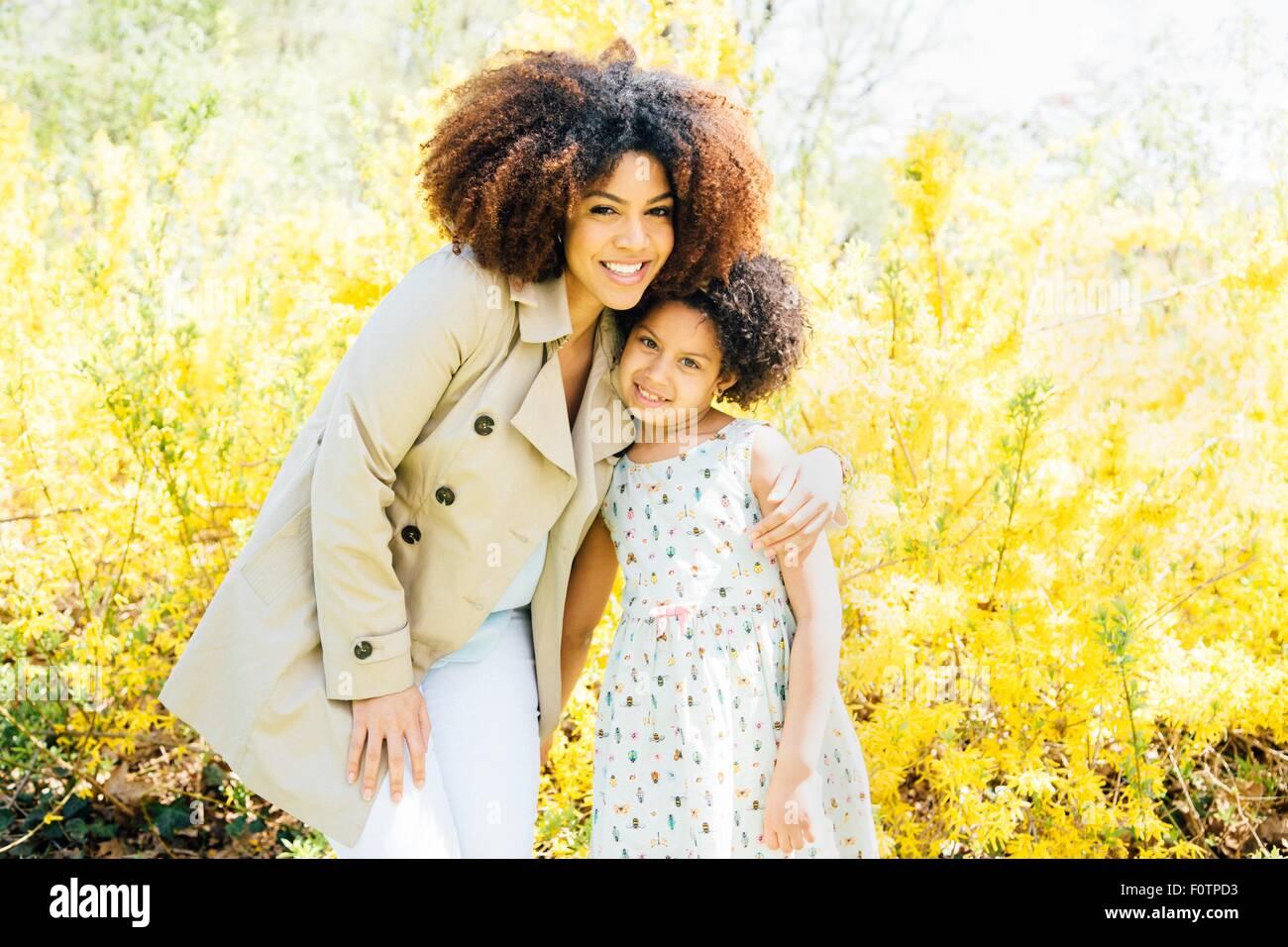 Retrato de madre con brazo alrededor de hija, mirando a la cámara, sonriendo Imagen De Stock
