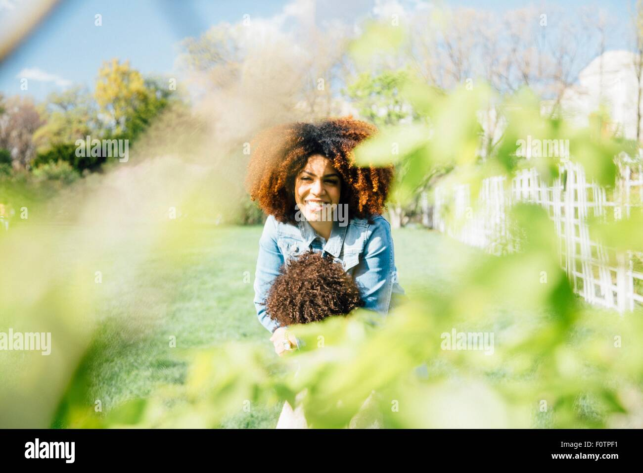 Vista a través del follaje de la madre hija abrazan sonrientes Foto de stock