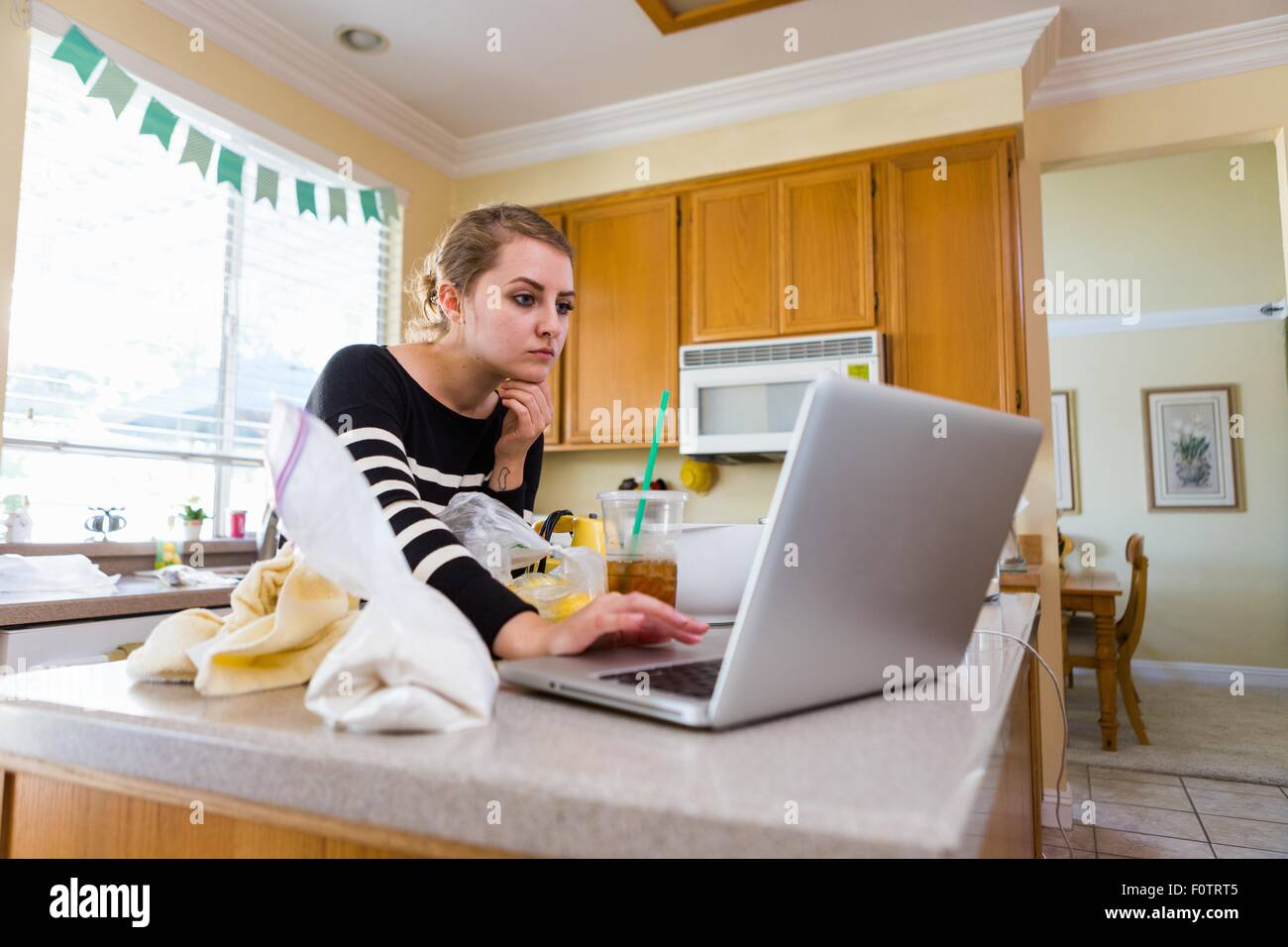 Mujer usando el portátil en la cocina Foto de stock
