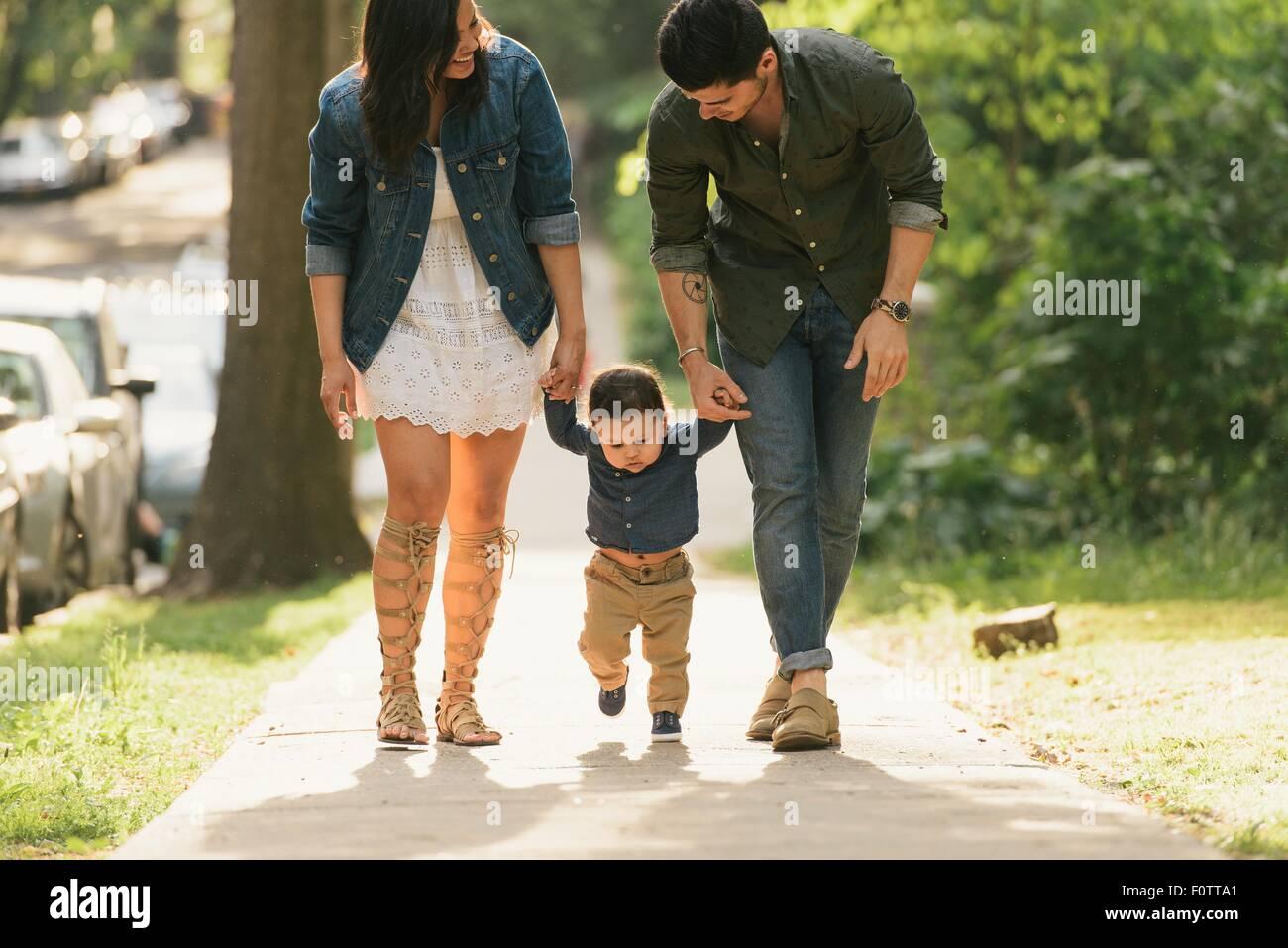 Vista del ángulo frontal de la madre y el padre sosteniendo bebés varones manos mientras camina Imagen De Stock