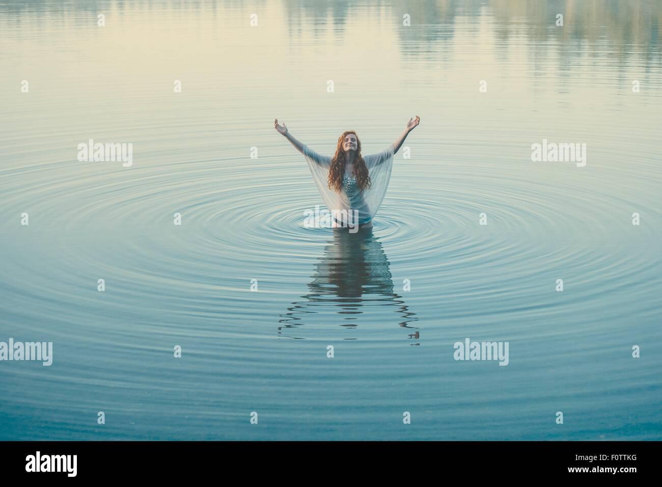 Mujer joven de pie en medio del lago ondulaciones con brazos abiertos Foto de stock