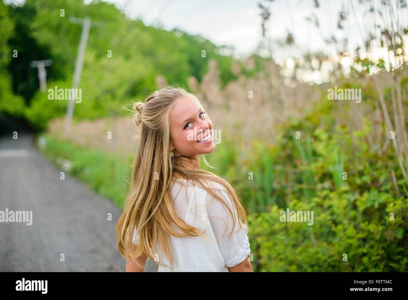 Retrato de mujer joven con largo pelo rubio mirando hacia atrás en los caminos rurales Foto de stock