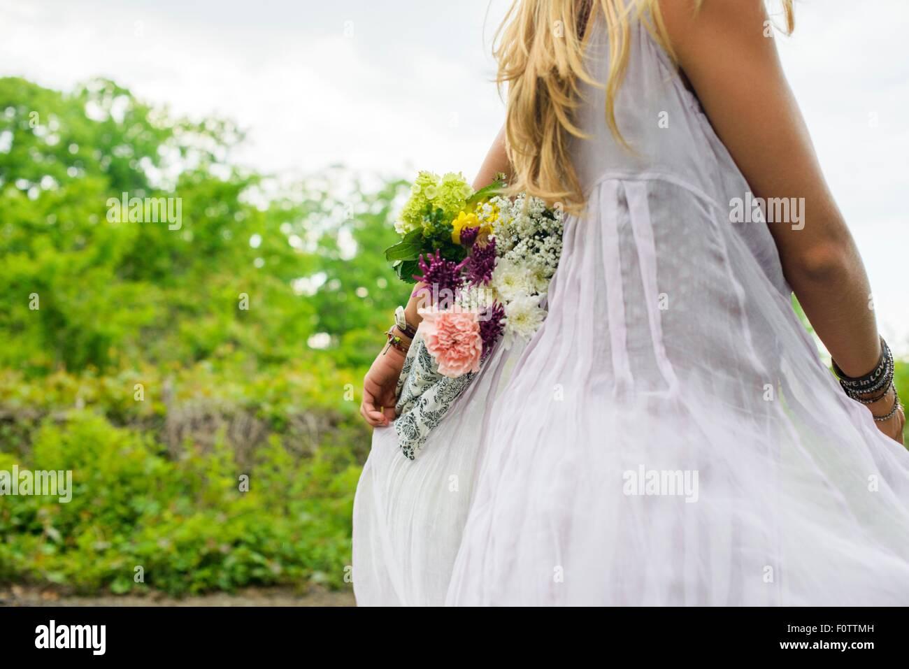 Captura recortada de joven mujer vistiendo vestido blanco llevar ramo de flores a la espalda Imagen De Stock