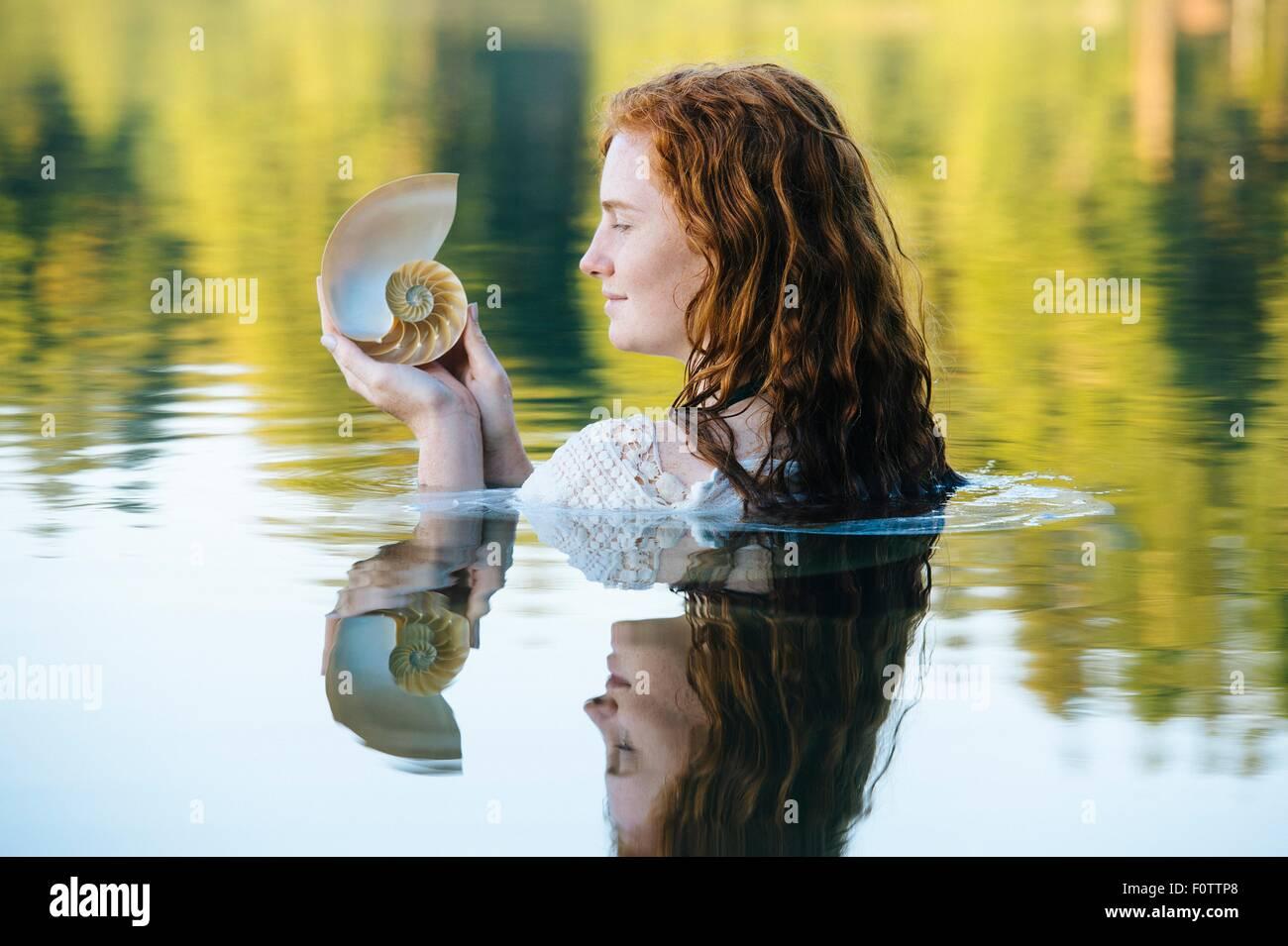 Cabeza y hombros de la mujer joven con largo pelo rojo en el lago contemplando el Seashell Foto de stock