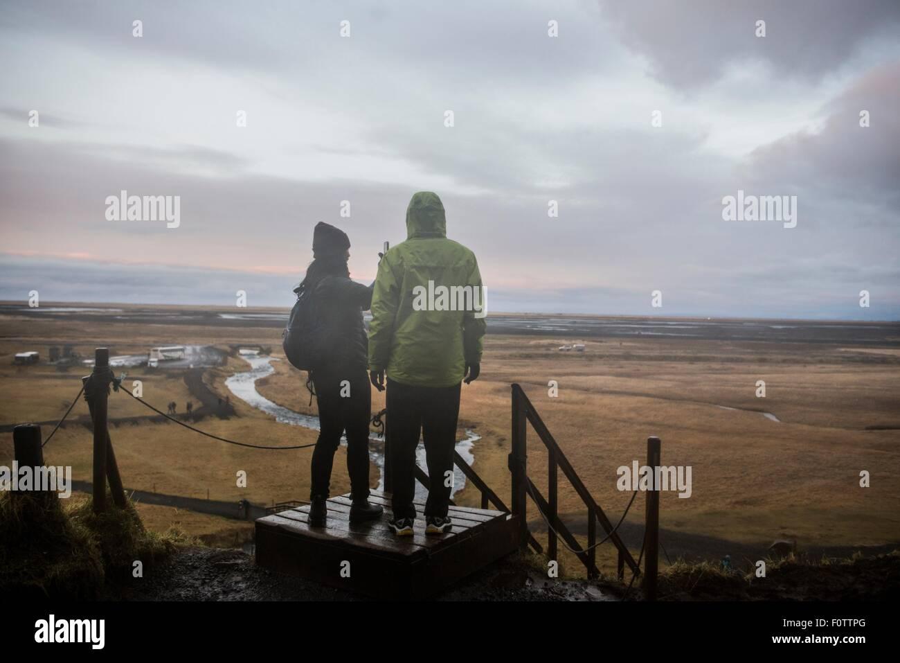 Hombres y mujeres turistas tomando fotografías desde la plataforma de observación de Seljalandsfoss, Islandia Imagen De Stock