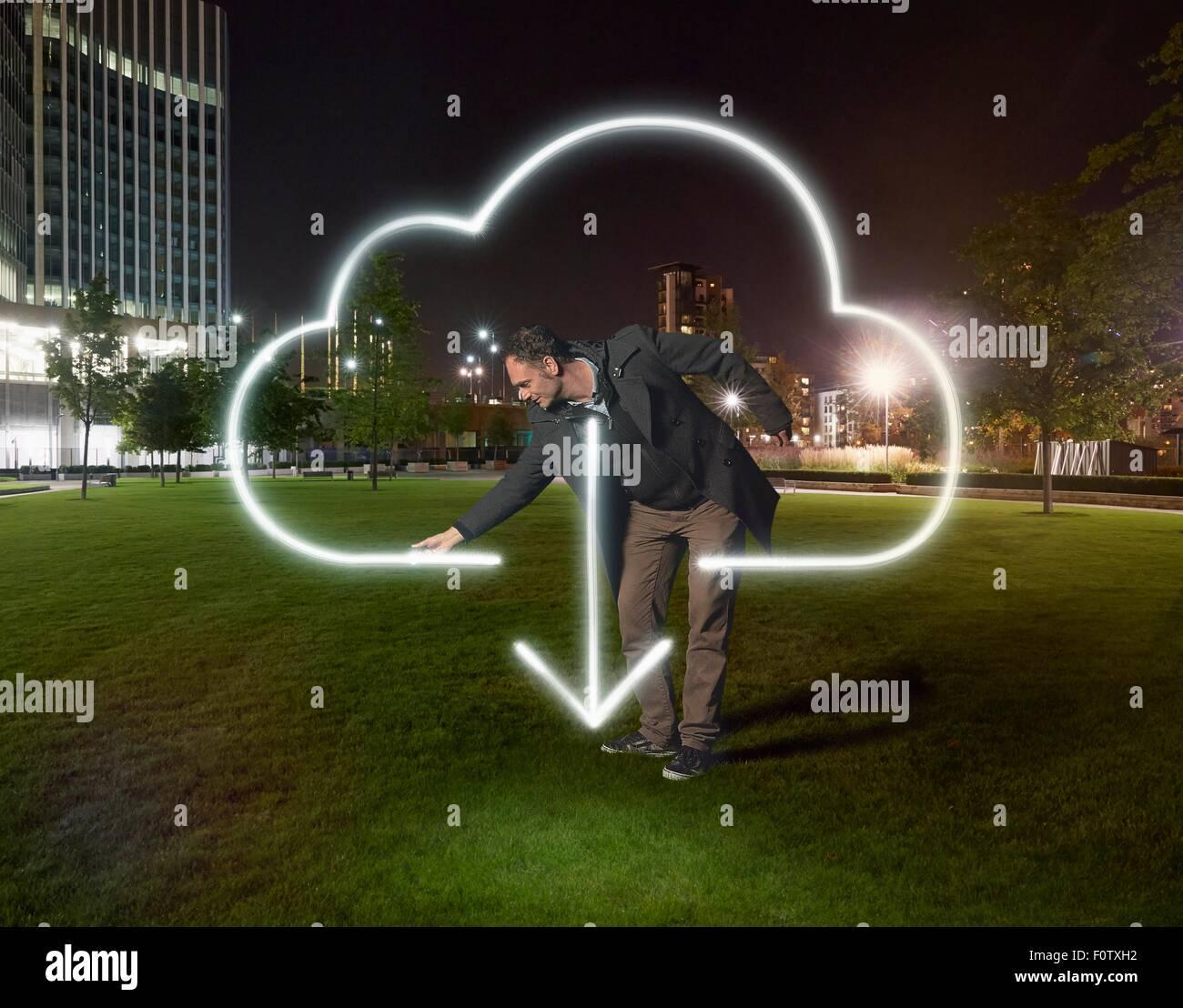 Símbolo descargar nube de pintura del artista fuera de edificio de oficinas en la noche Imagen De Stock