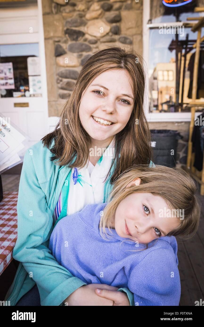 Mujer joven y chica sonriente hacia la cámara, Retrato Imagen De Stock