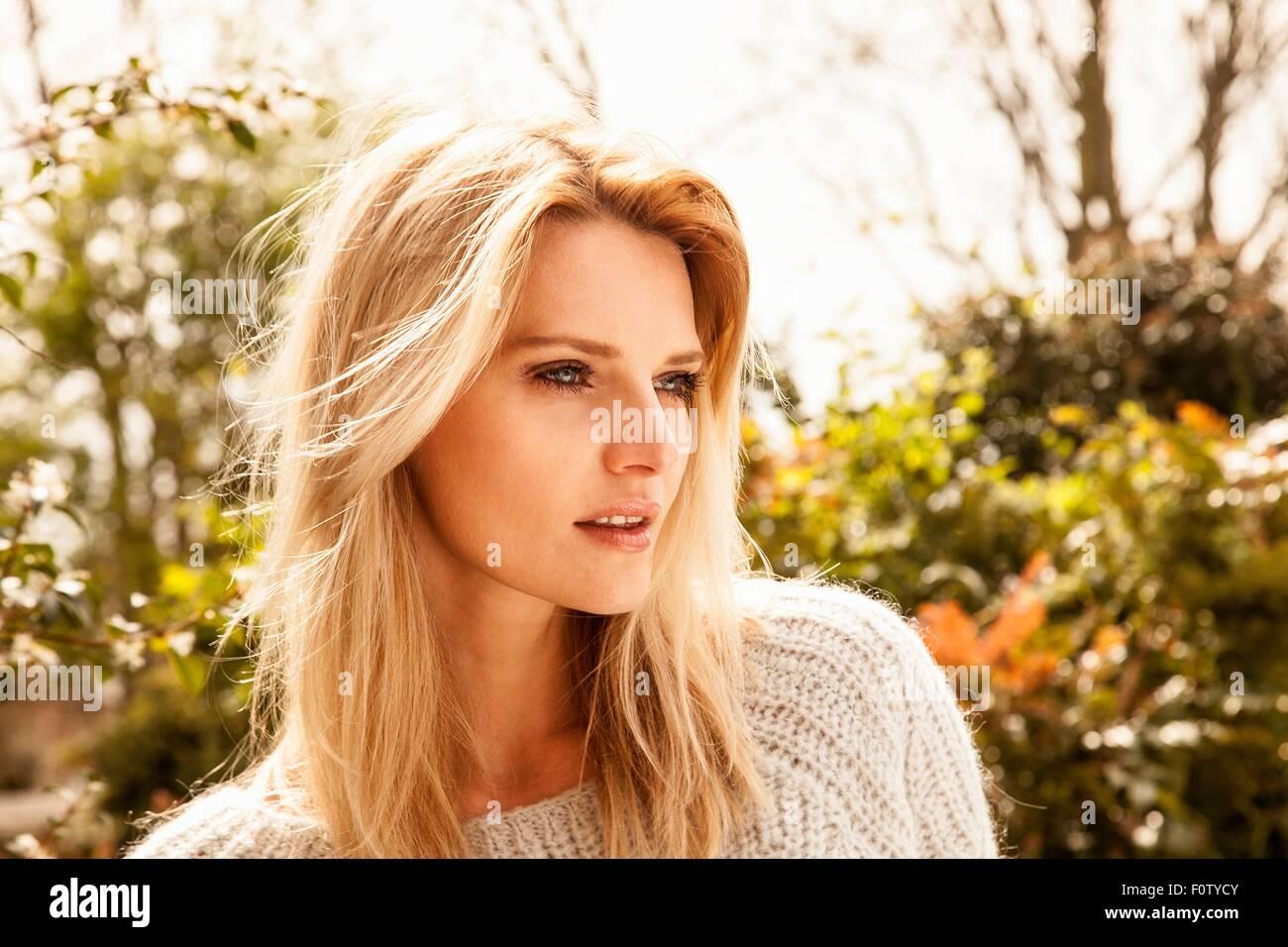 A mediados hermosa mujer adulta con largo pelo rubio en el jardín Foto de stock