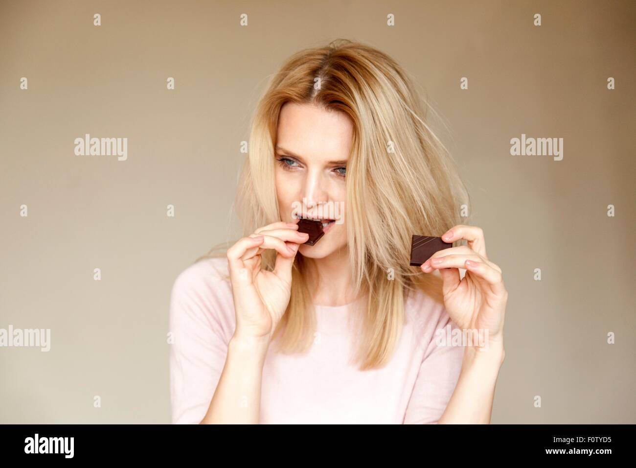 Retrato de mujer hermosa con largo pelo rubio comer chocolate bar Imagen De Stock
