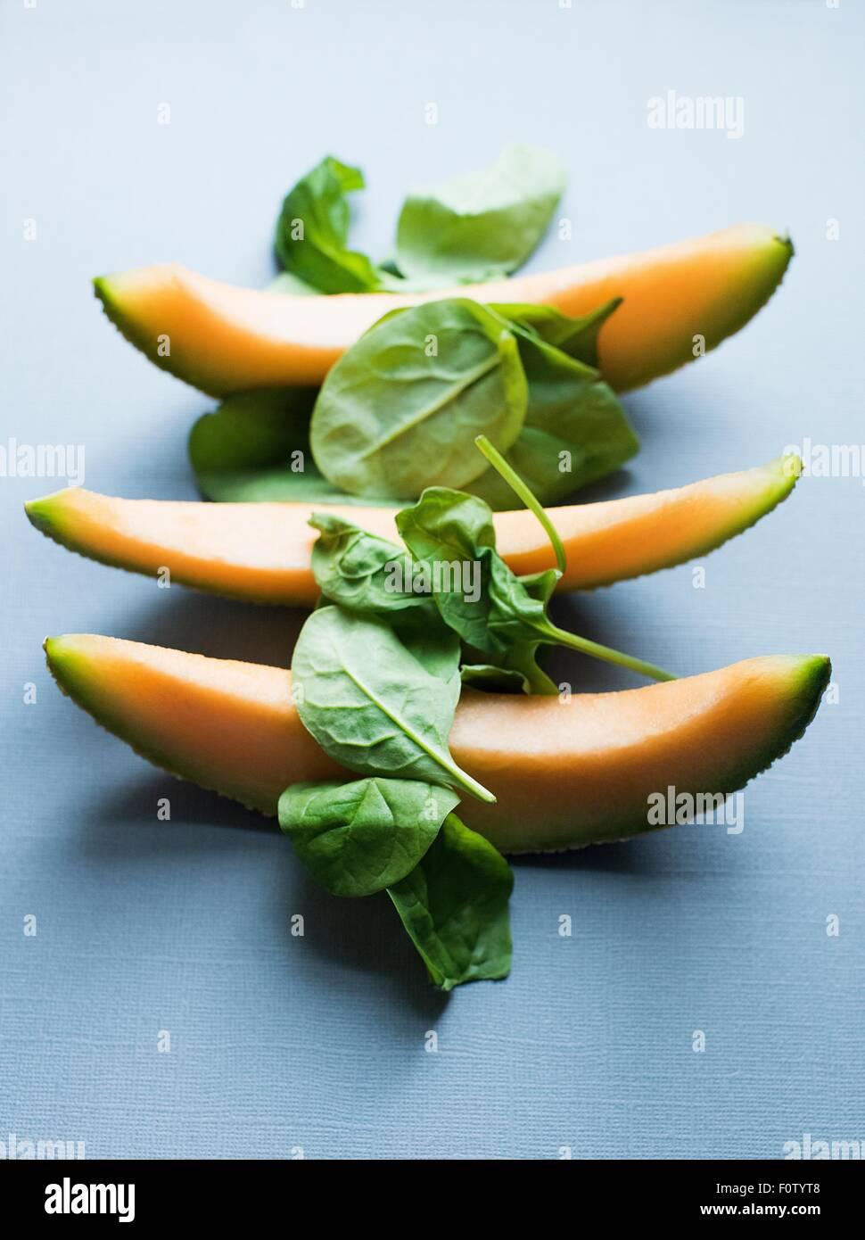 Tres rebanadas de melón fresco y espinacas. Imagen De Stock