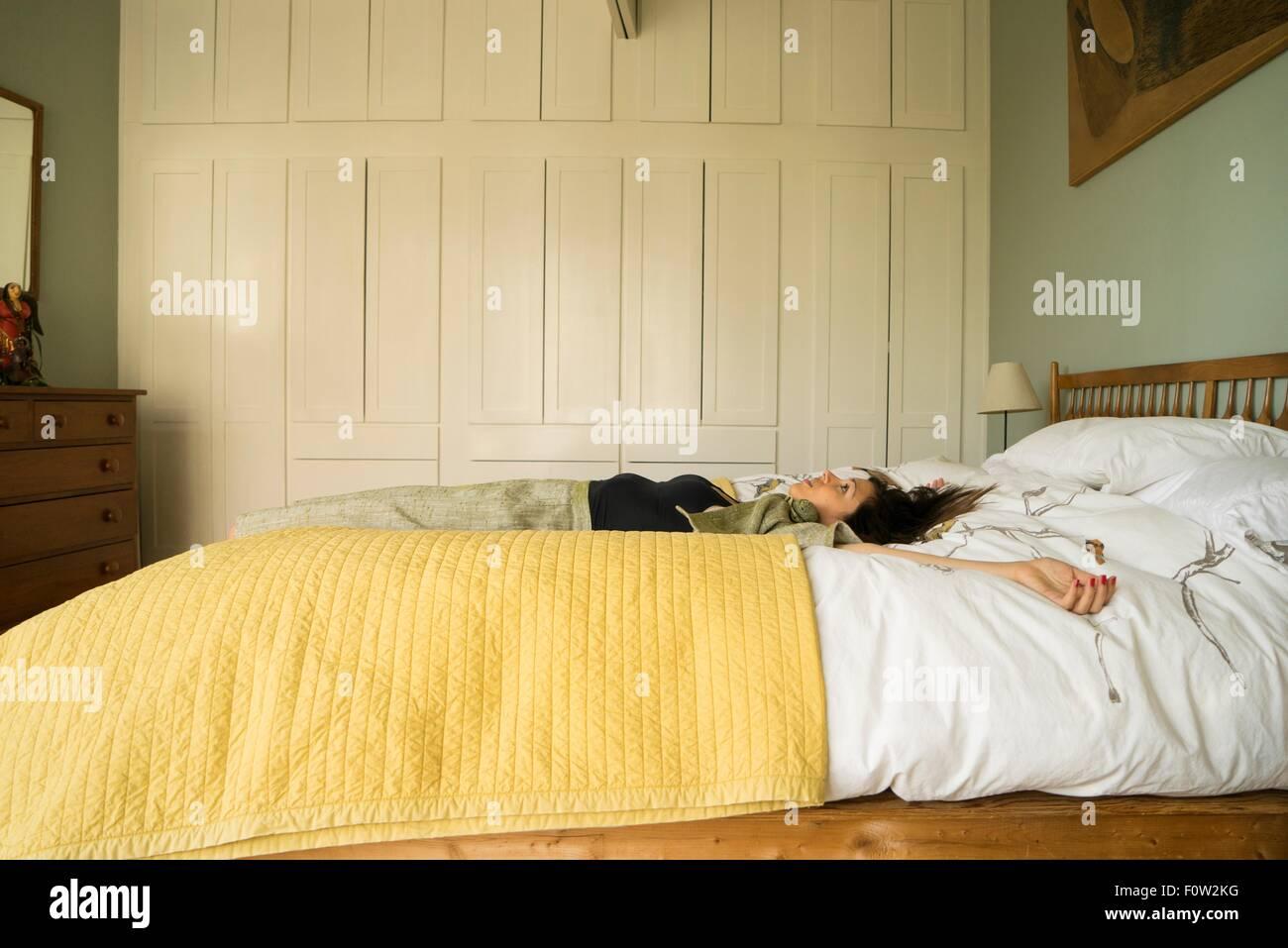 Vista lateral de la mujer que estaba acostada en la cama con los brazos abiertos Imagen De Stock