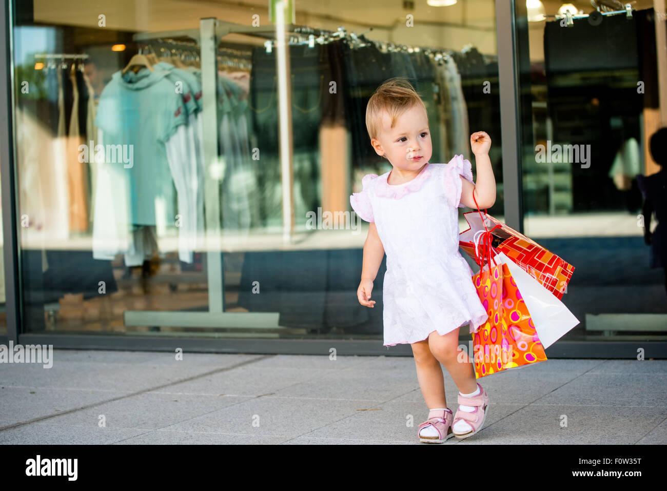 Lindo bebé pasa con bolsas de compras, tiendas en segundo plano. Imagen De Stock